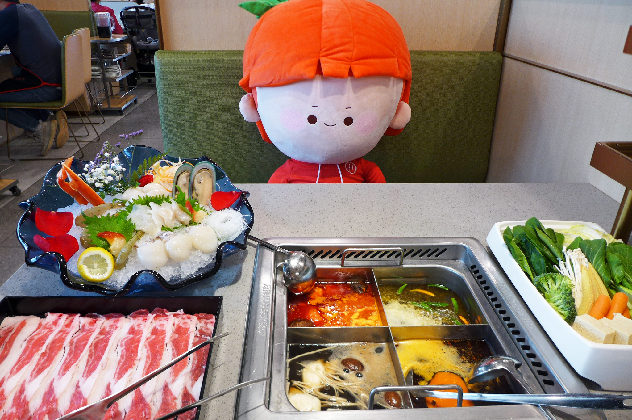 A stuffed tomato character with a red hat sits opposite me at a booth, with a hot pot meal spread before us
