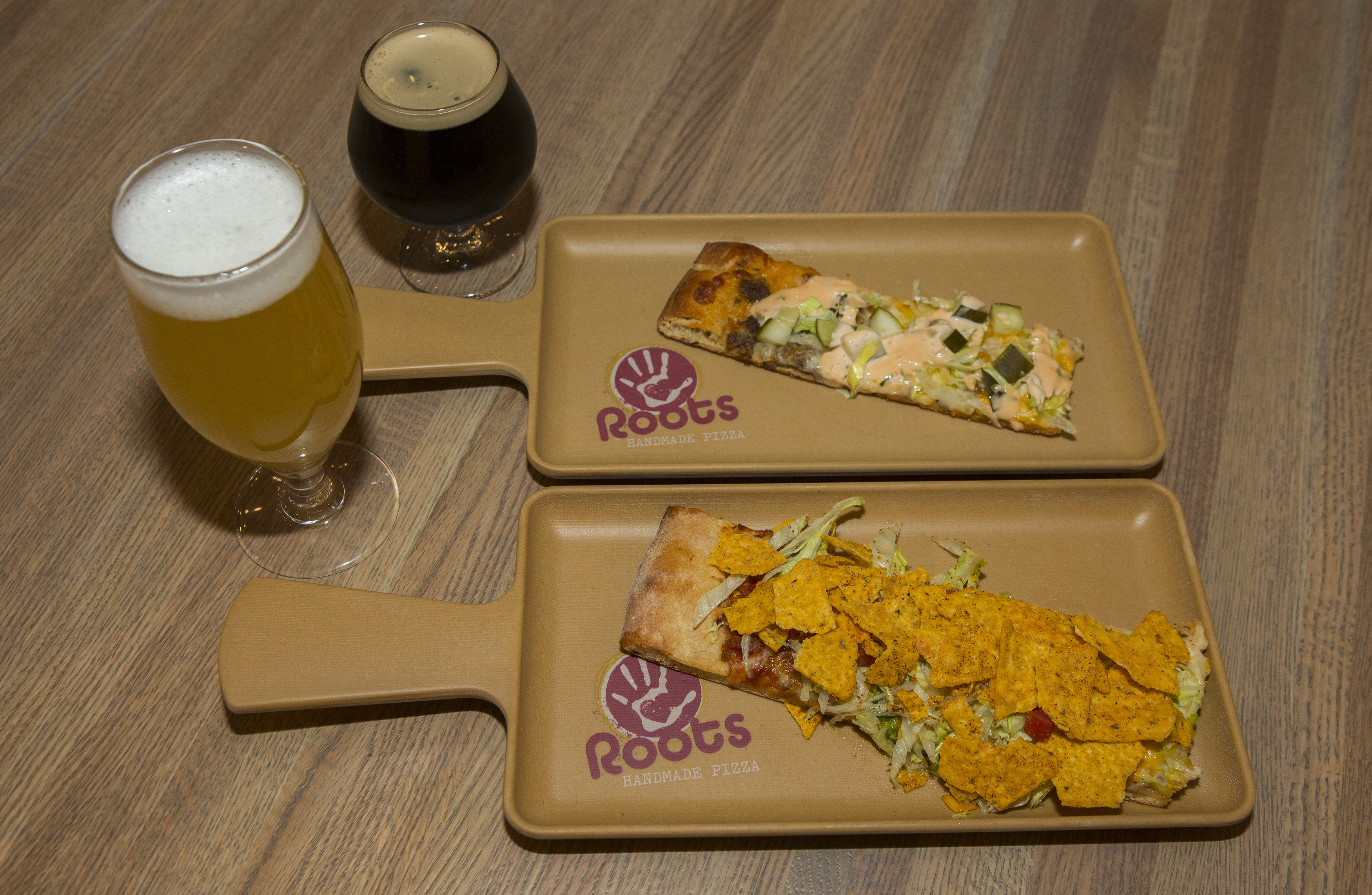 A lager and dark beer in tulip glasses next to two trays with a strip of Quad City pizza.