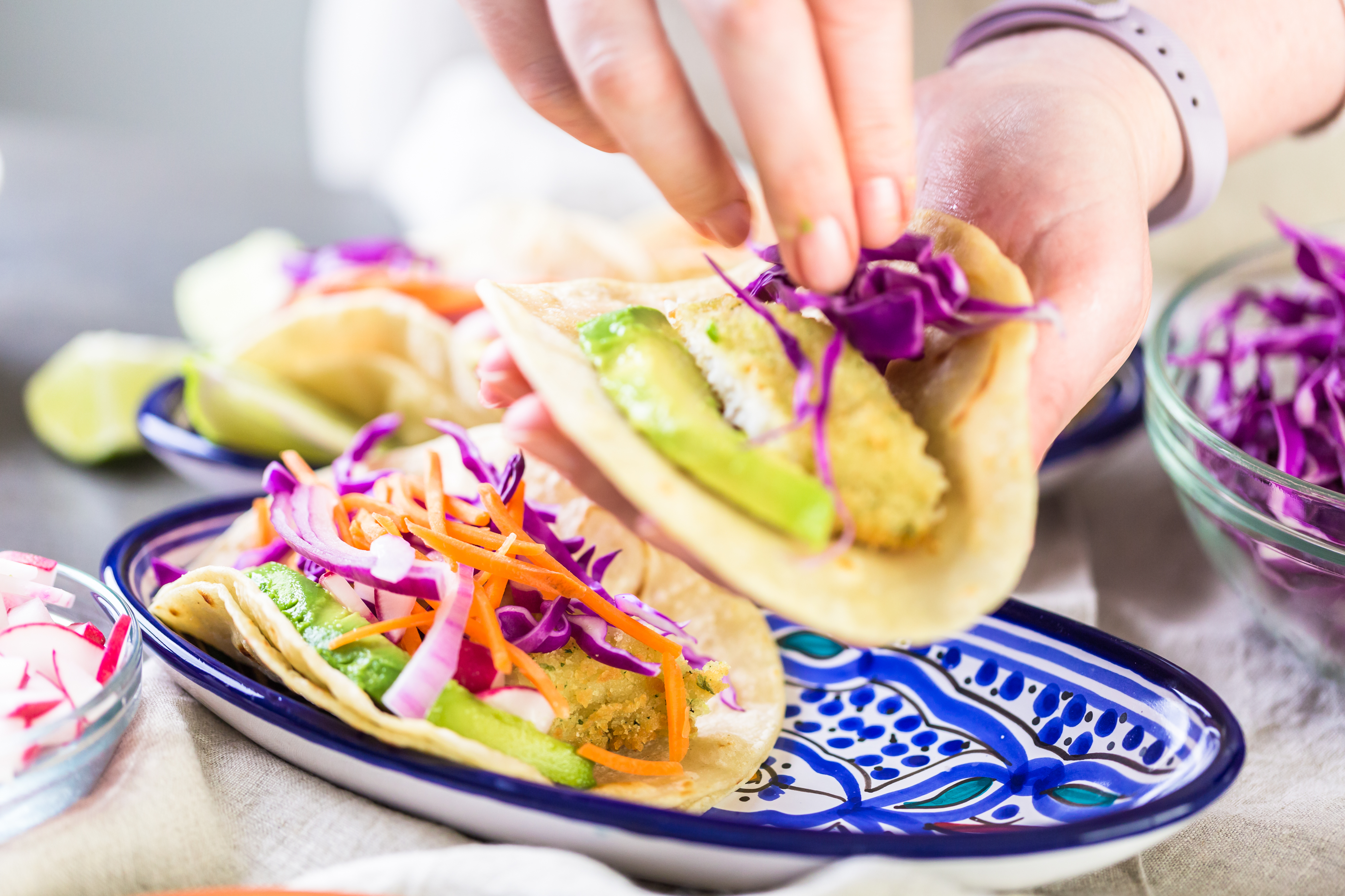 Women adds cabbage to the top of a fish taco.