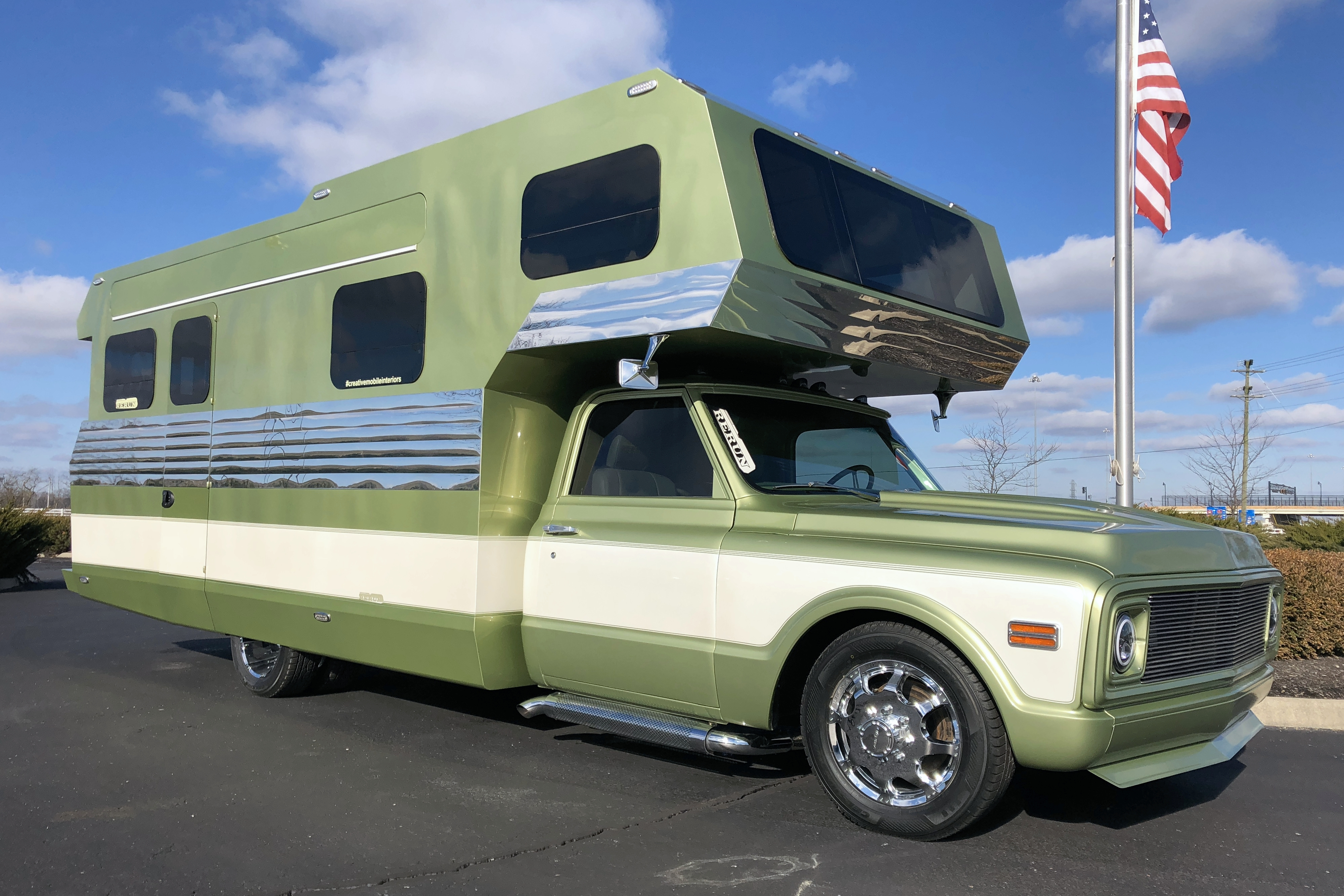 An avocado-colored vintage camper has an over-the-cab sleeping area, cream trim, and a sleek silver plated stripe down the center.