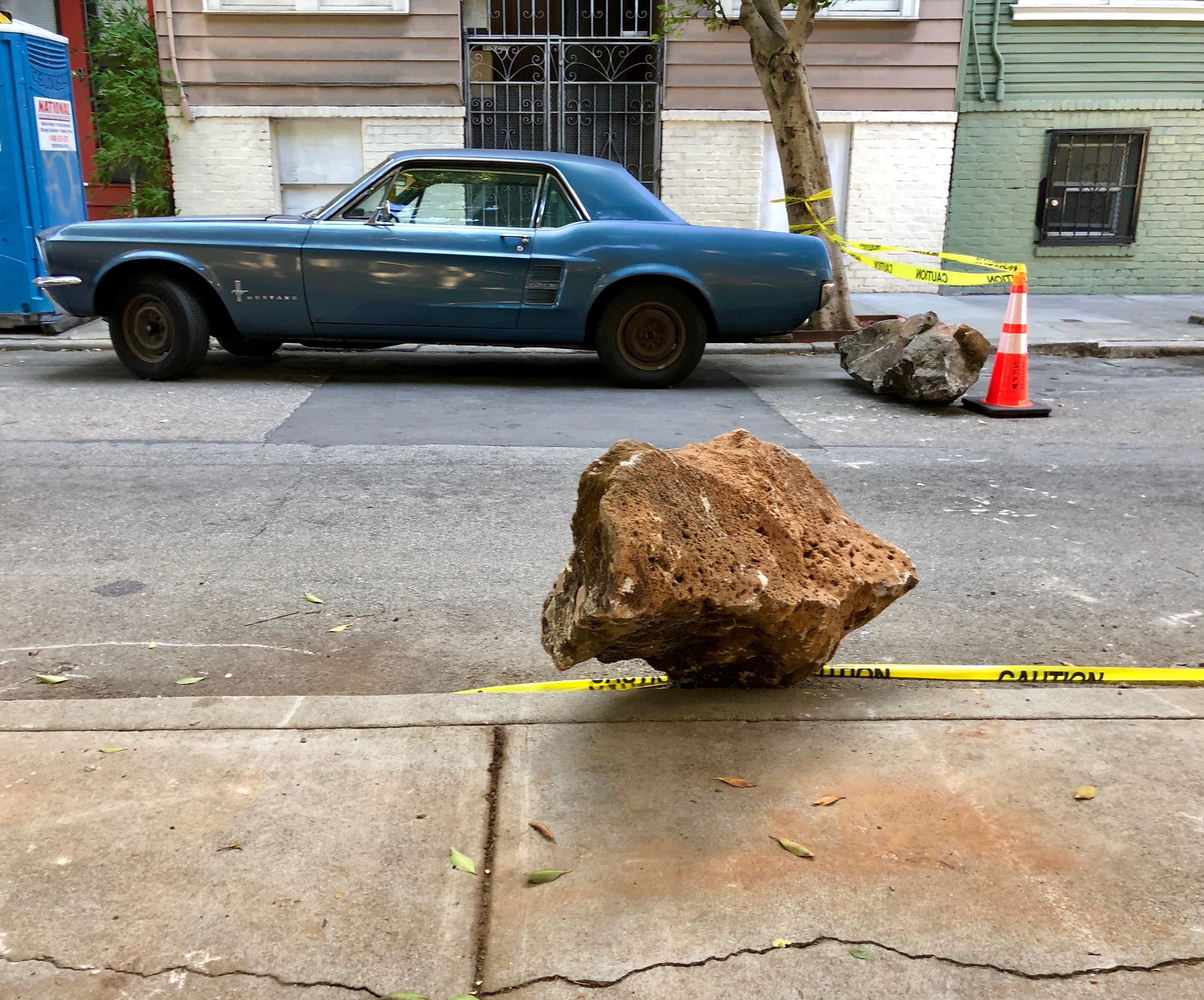 A sidewalk with a bolder on it. On the other side of the street sits a blue Mustang car with a boulder next to its back bumper.