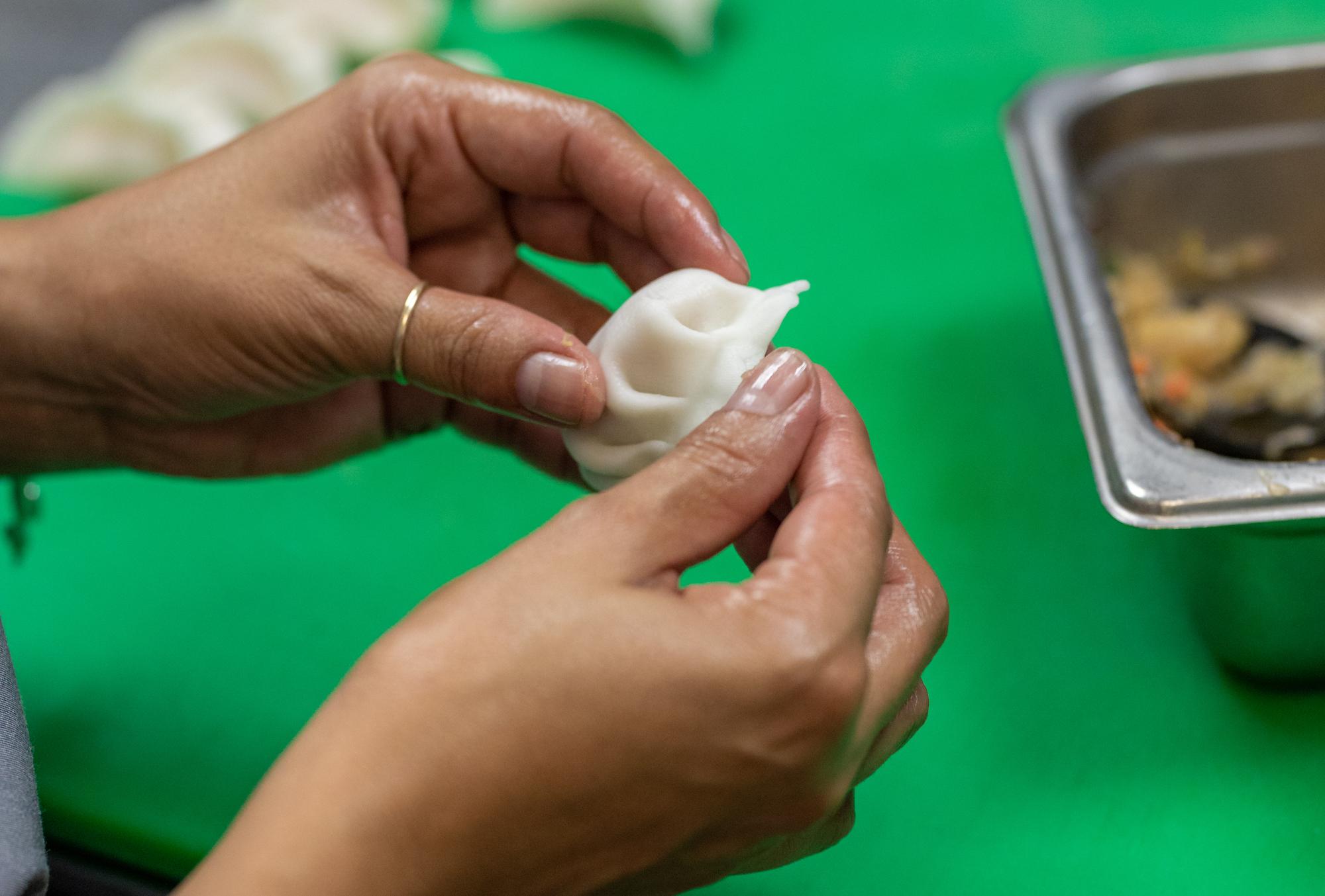 Hands wrap a dumpling over a bright green cutting board.