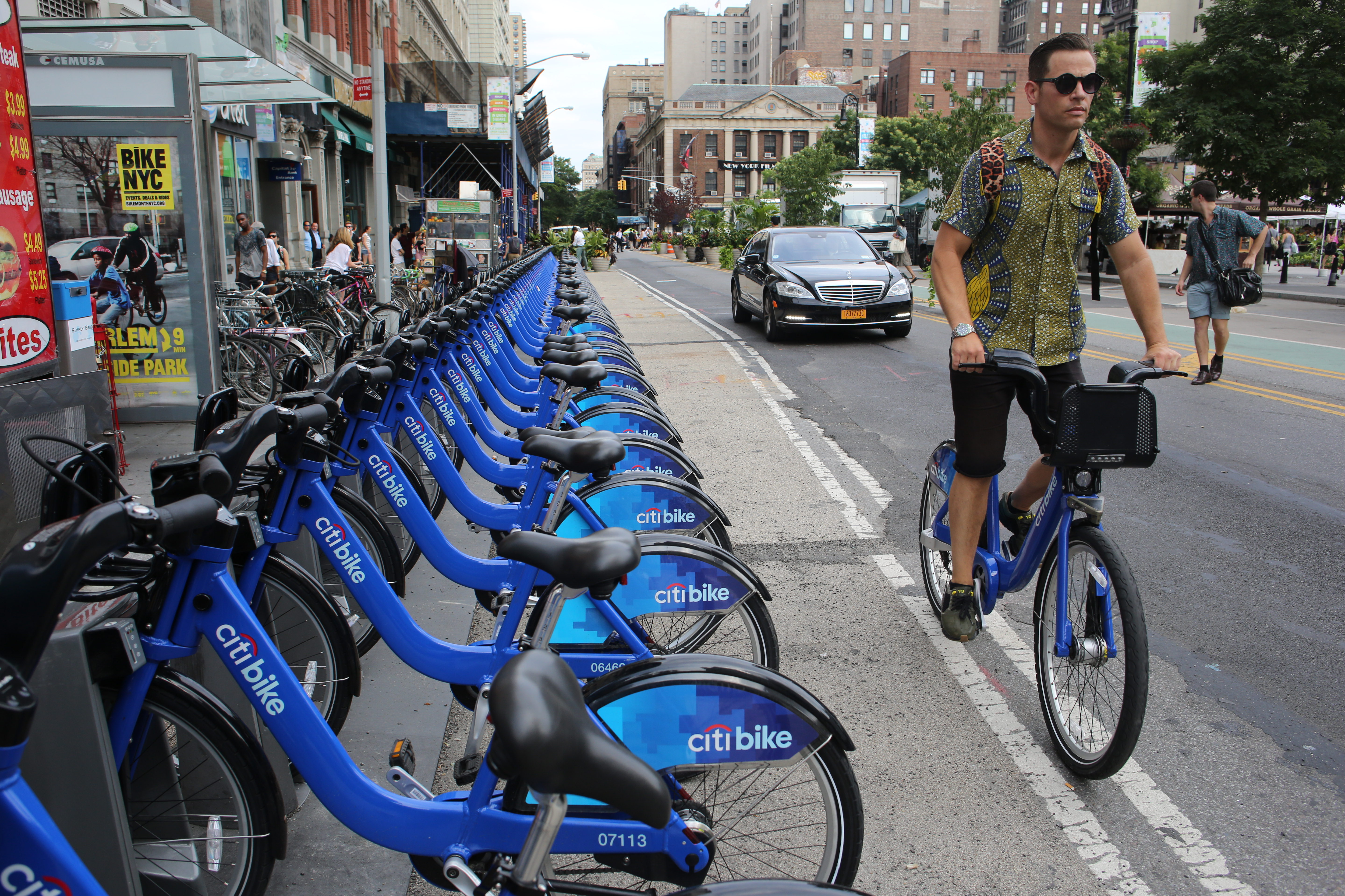 A rack of bright blue Citi Bikes. On the right, a man rides by the rack on a blue Citi Bike.