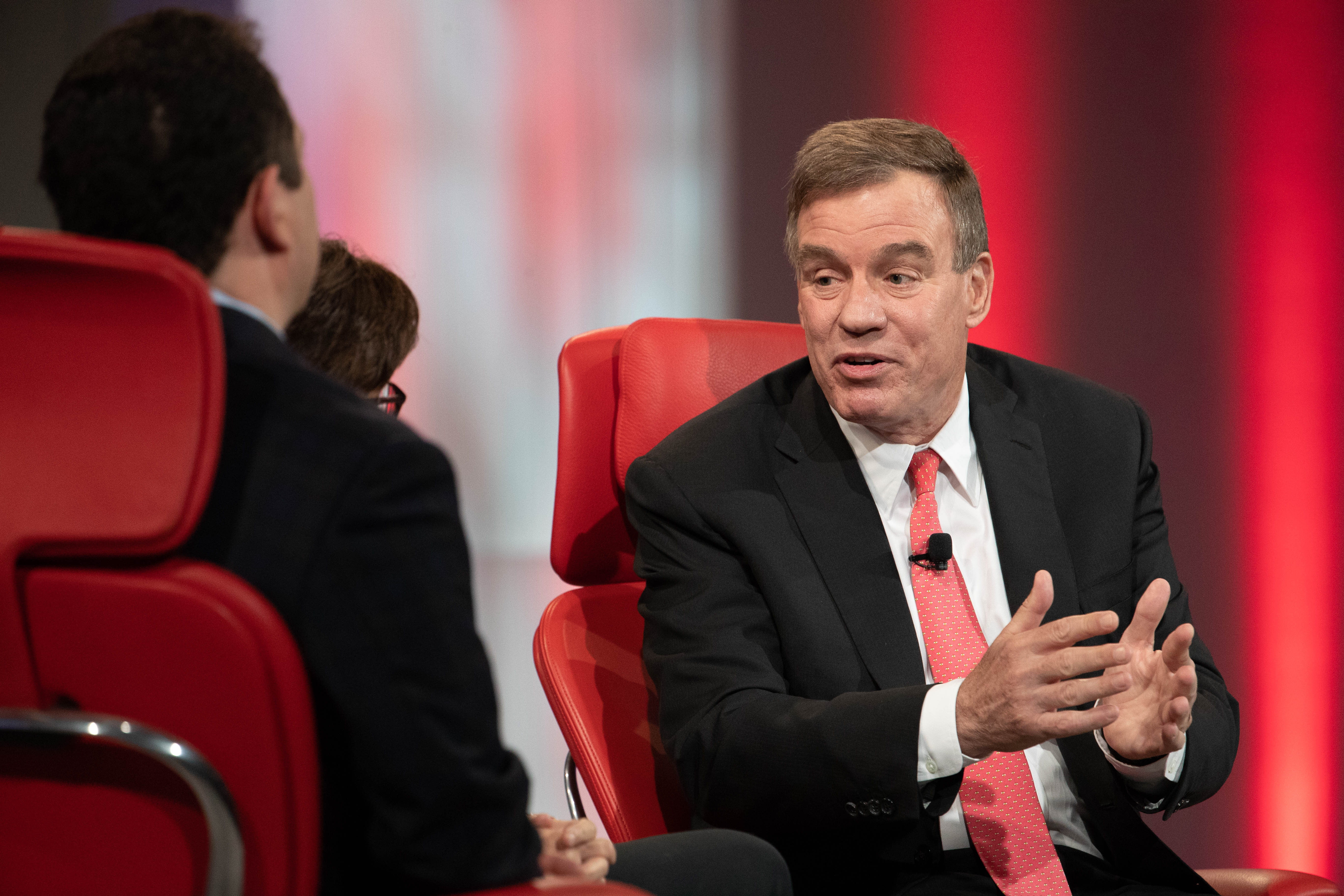 US Senator Mark Warner speaking onstage while seated in a red chair.