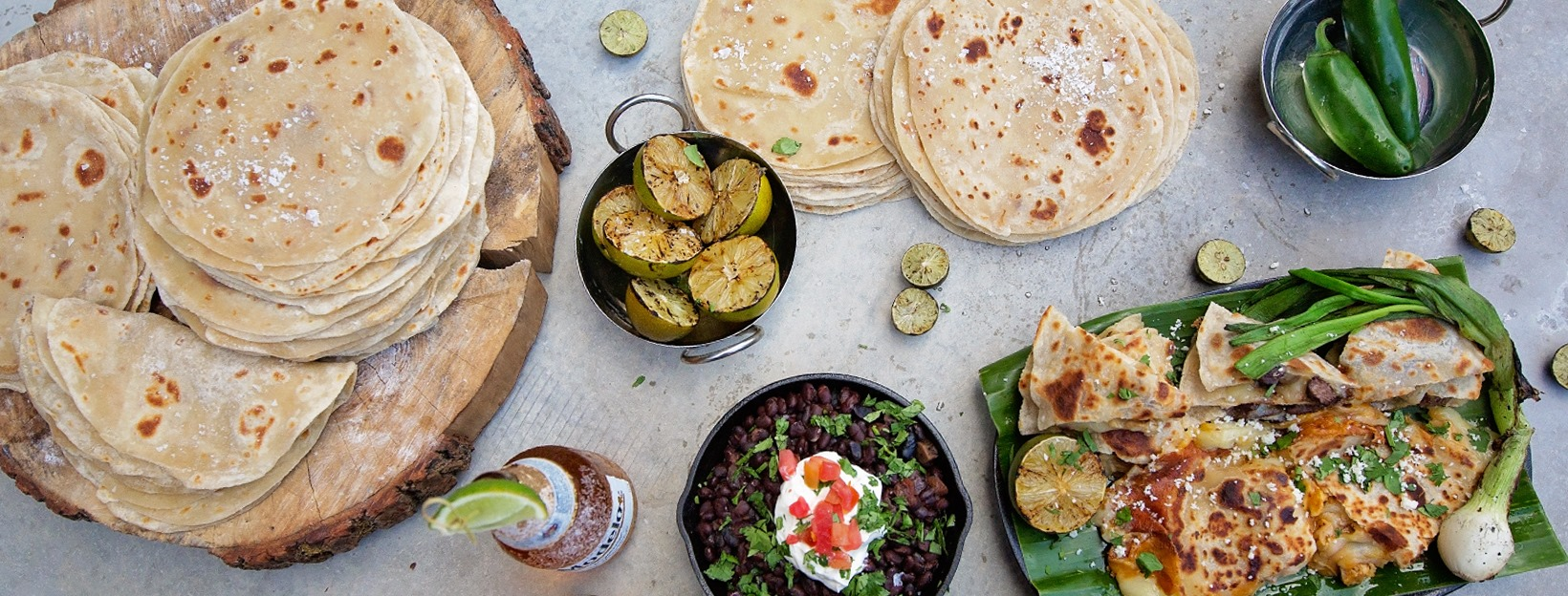 Tortillas, grilled limes, beer, beans, and quesadillas on a concrete background