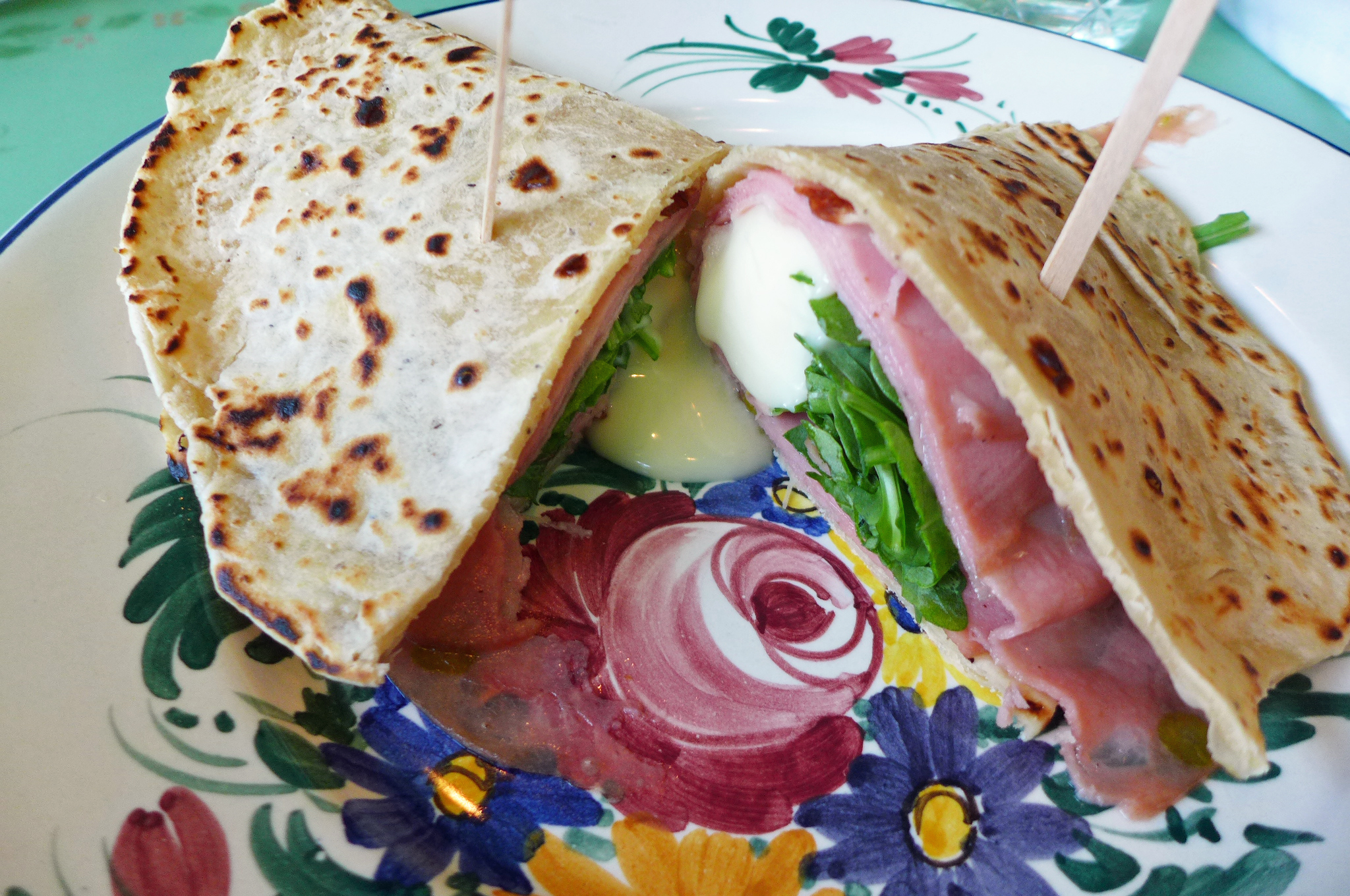 A flatbread sandwich with the dappled bread folded over meat and cheese on a flowered plate...