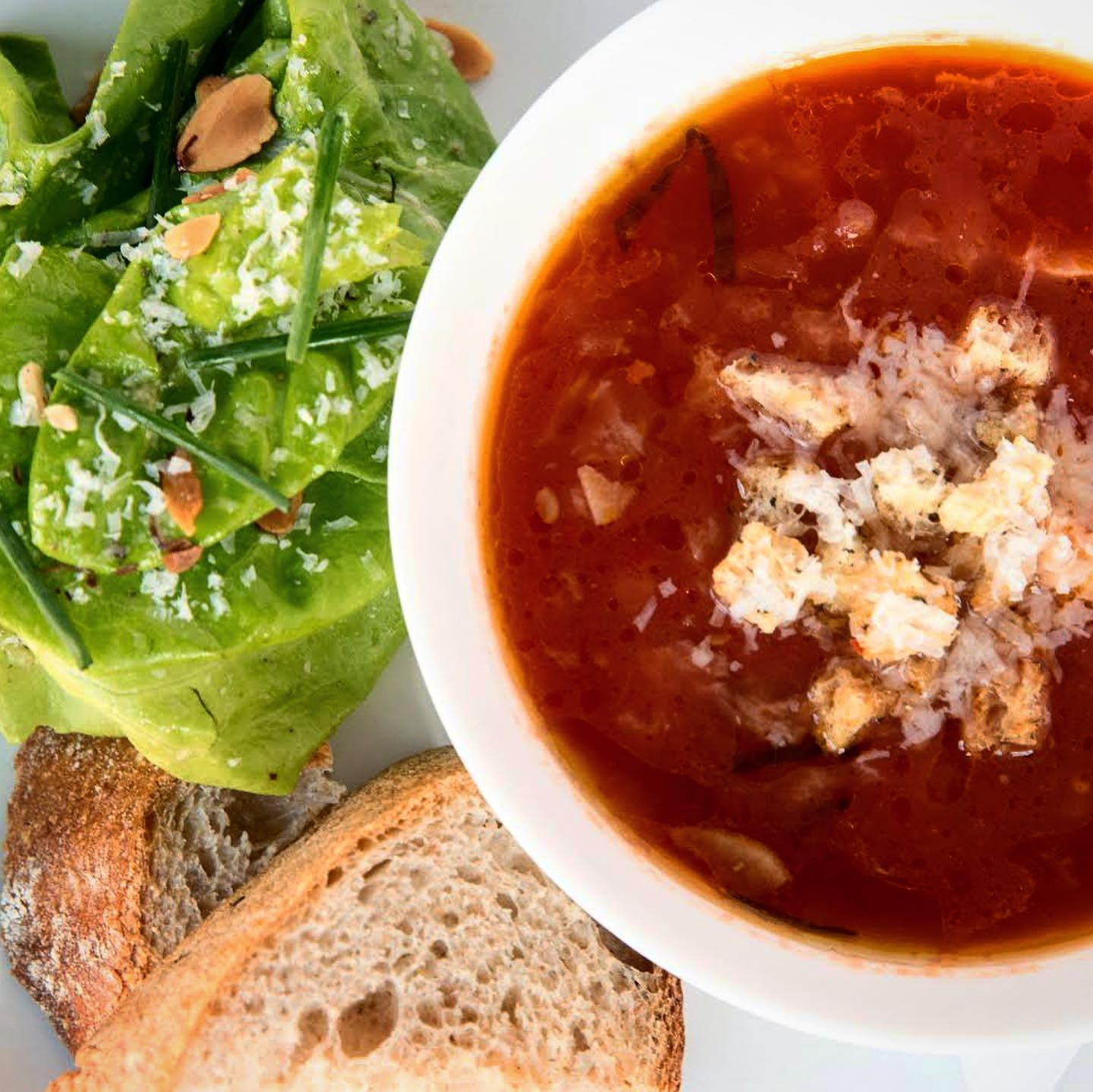 A bowl of bright red tomato soup topped with crumbles of bread and shreds of cheese on a white plate alongside slices of crusty bread and a small green salad