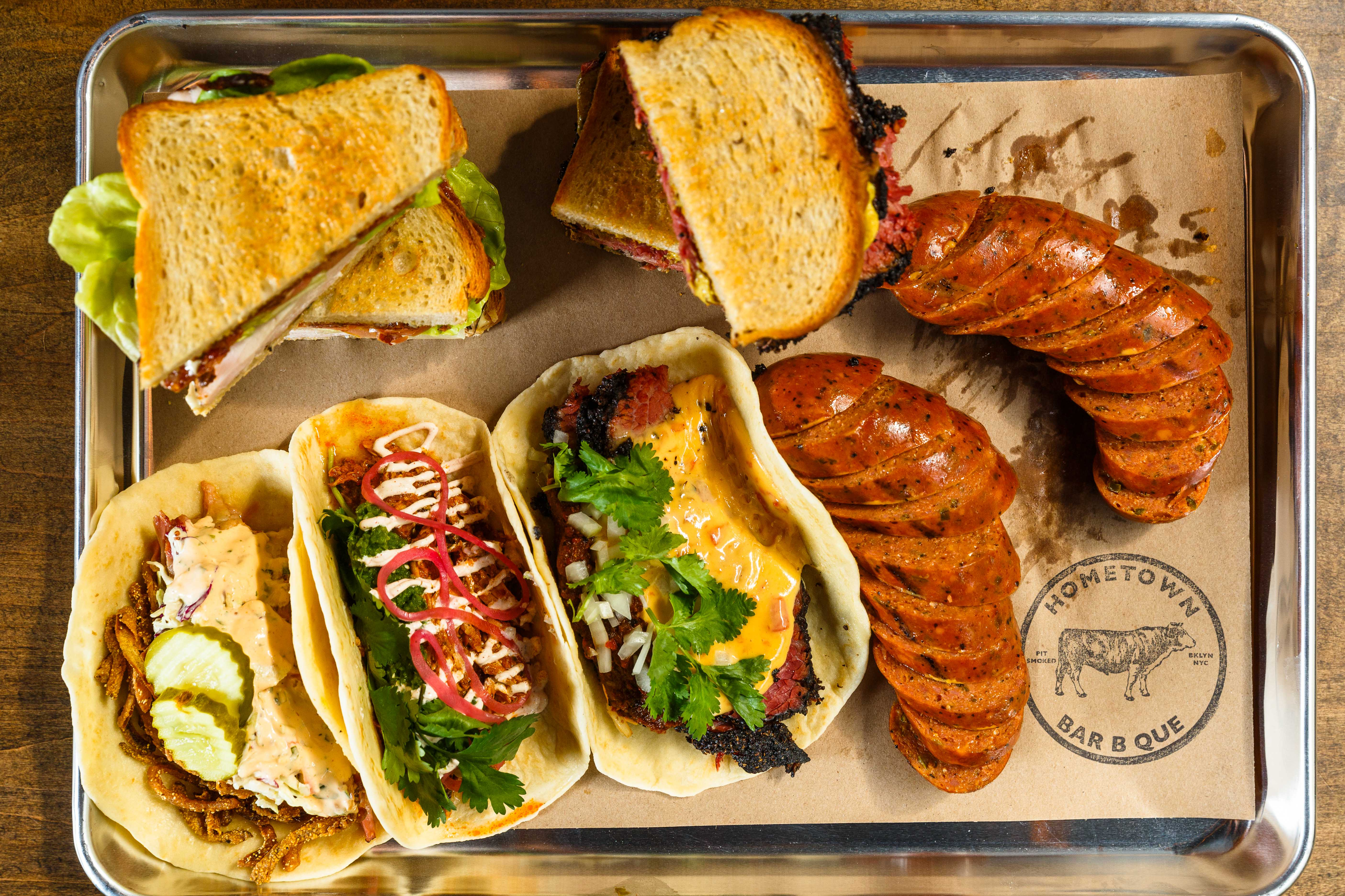 Three tacos, a turkey club, a pastrami sandwich, and sausage on a metal tray