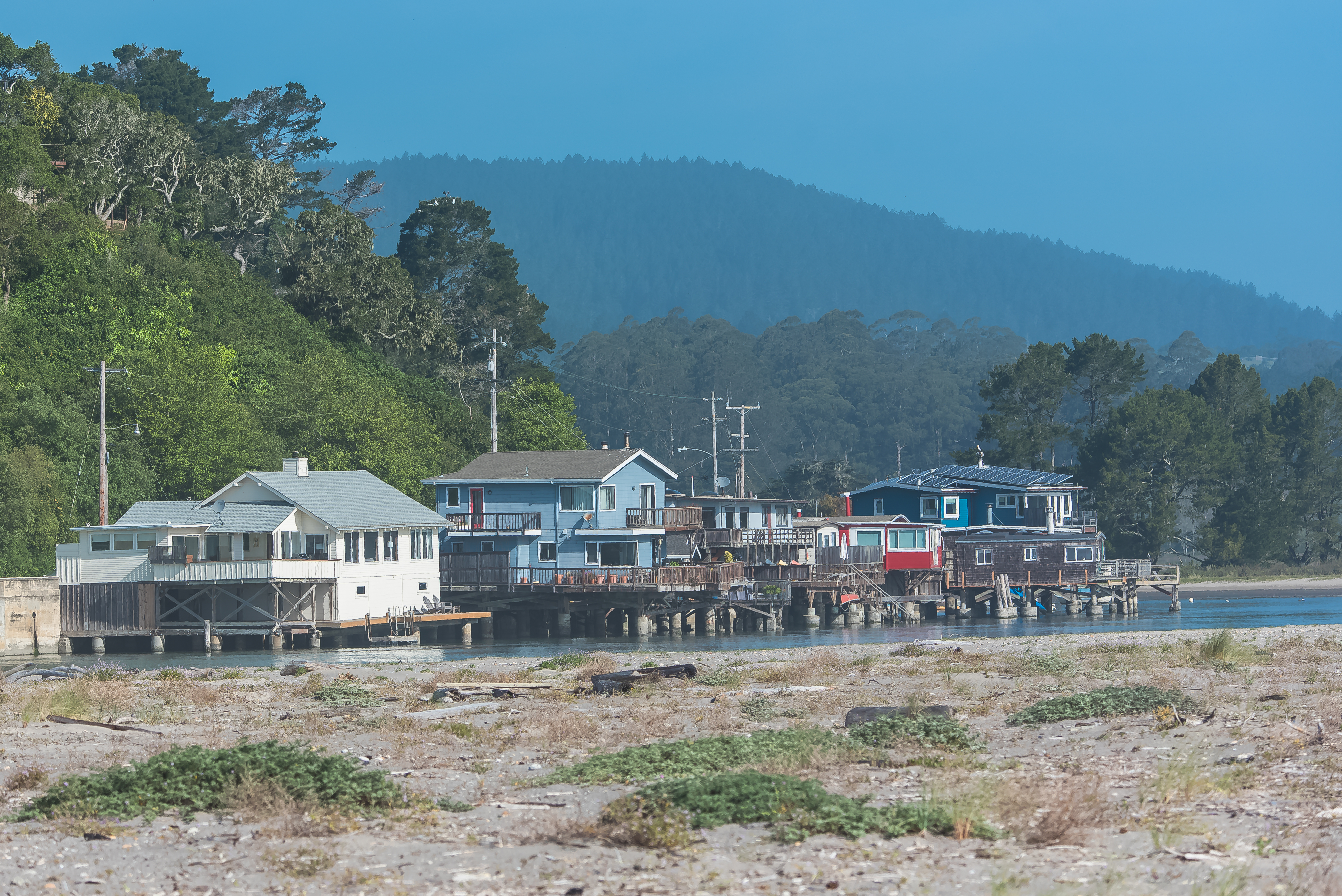 A handful of one- to two-story homes along the beach, with trees and mountainous terrain in the background.