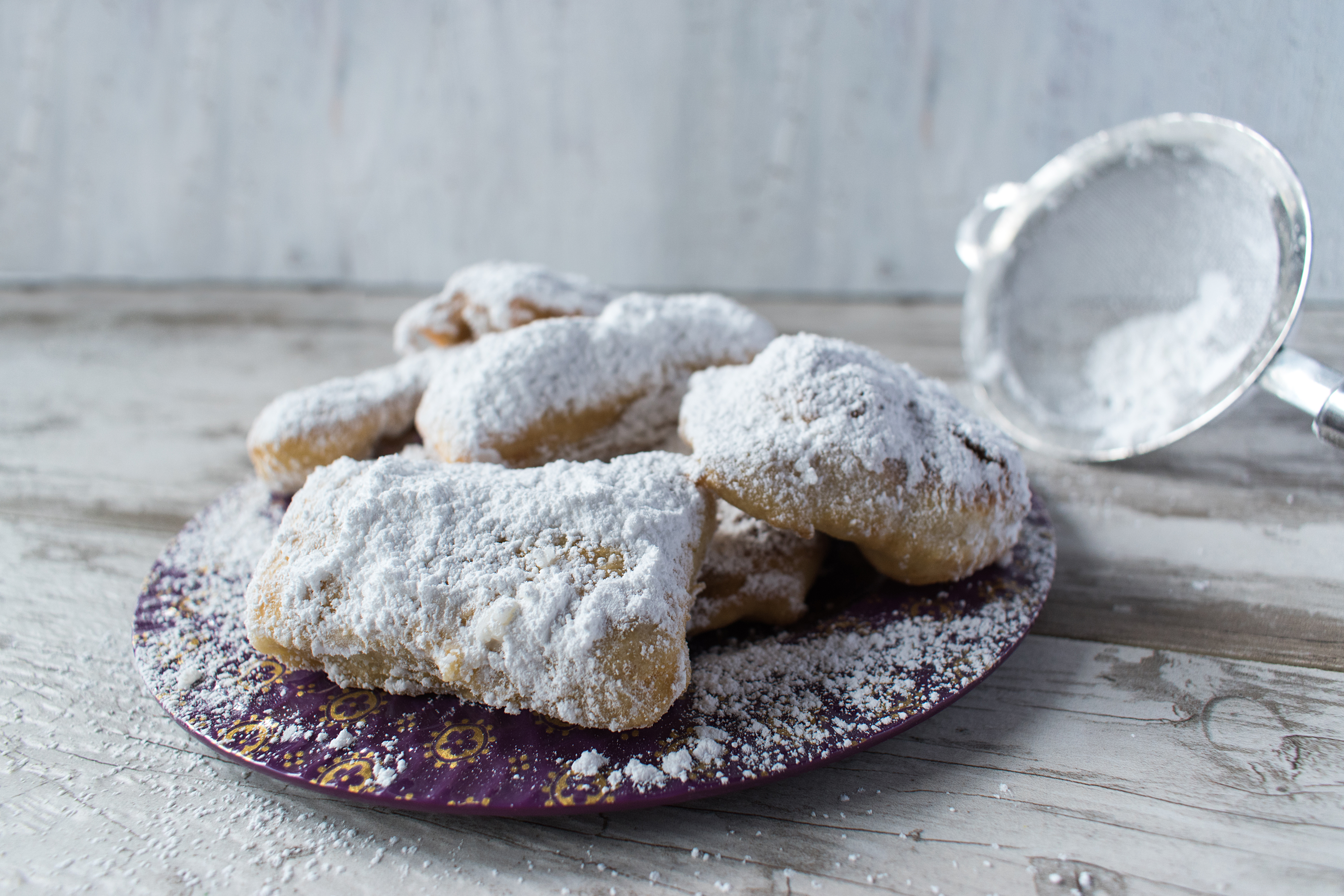 A plate of fluffy beignets covered in powdered sugar.