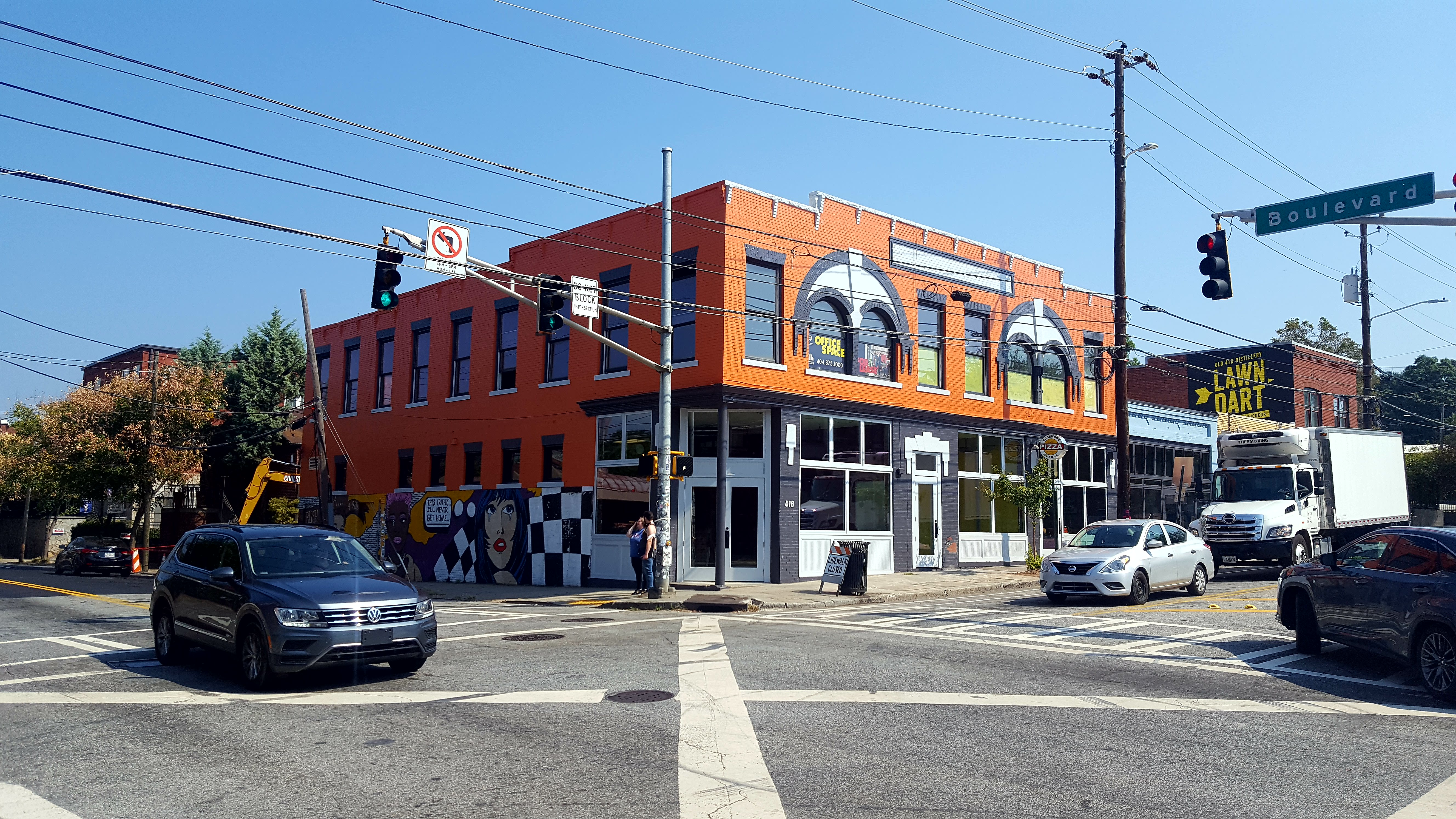 An old orange and white building is adorned with a mural on its left side.