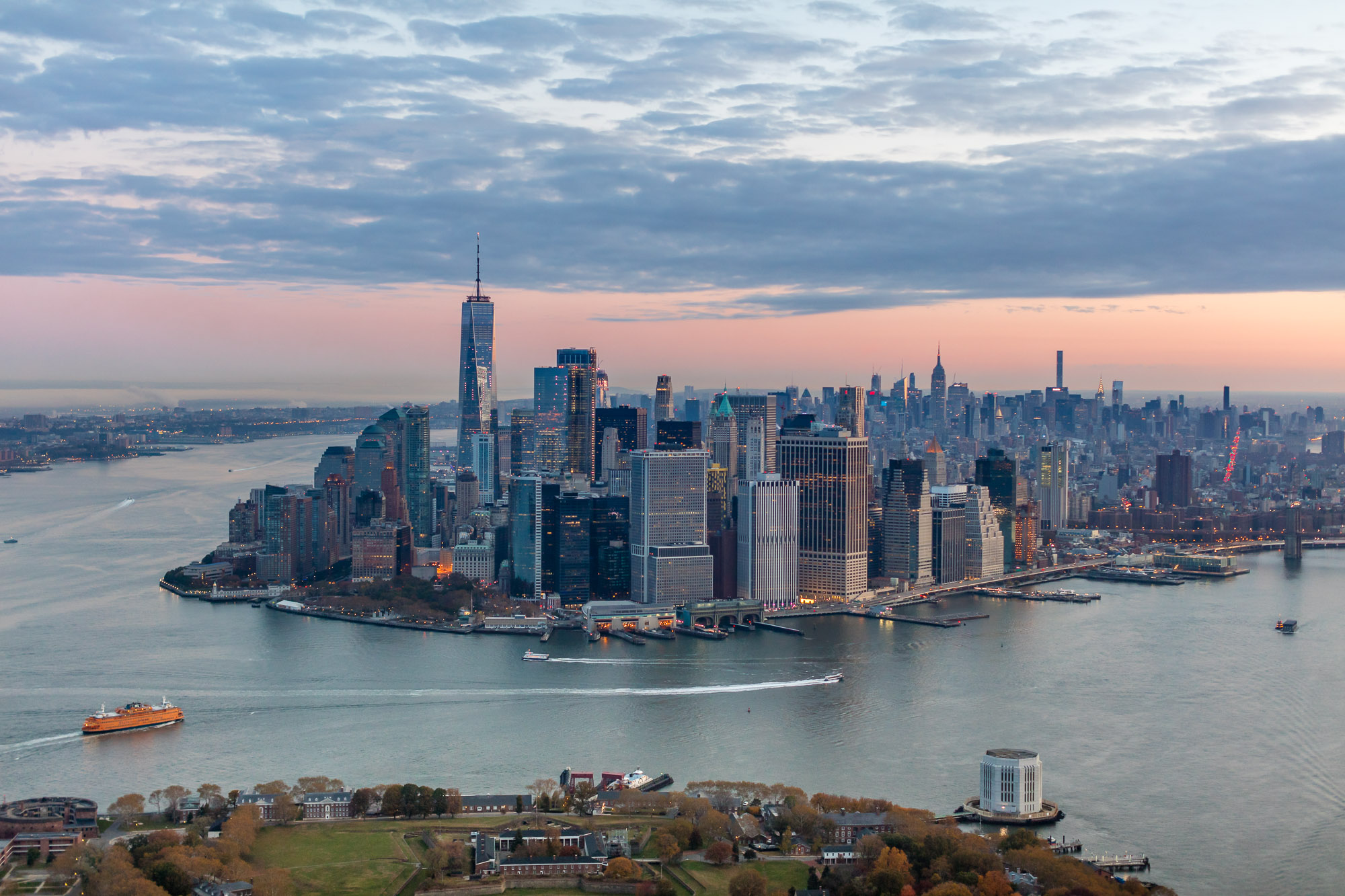 An arial view of several skyscraper buildings in lower Manhattan surrounded by the East and Hudson rivers.