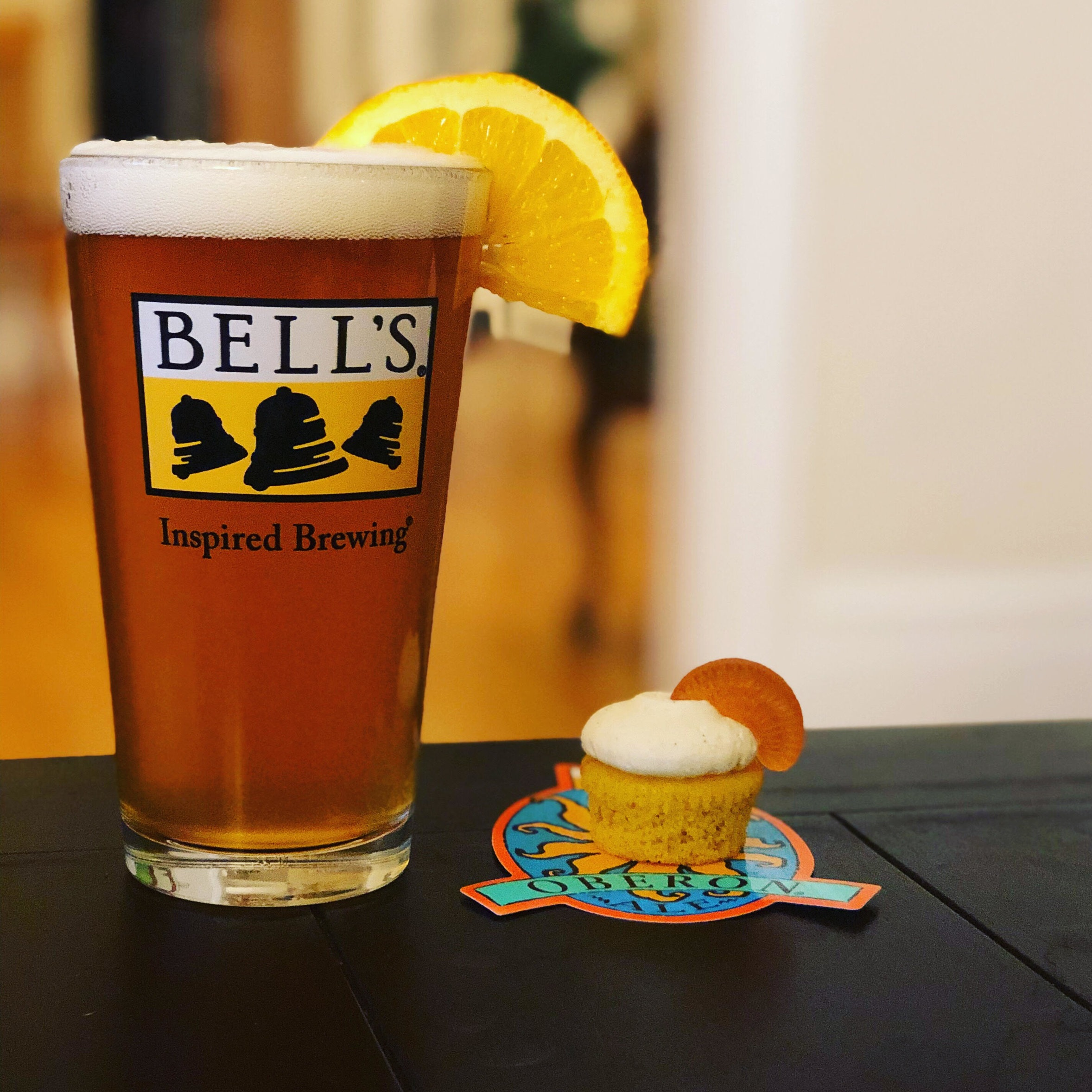 A glass of beer beside a small cupcake.