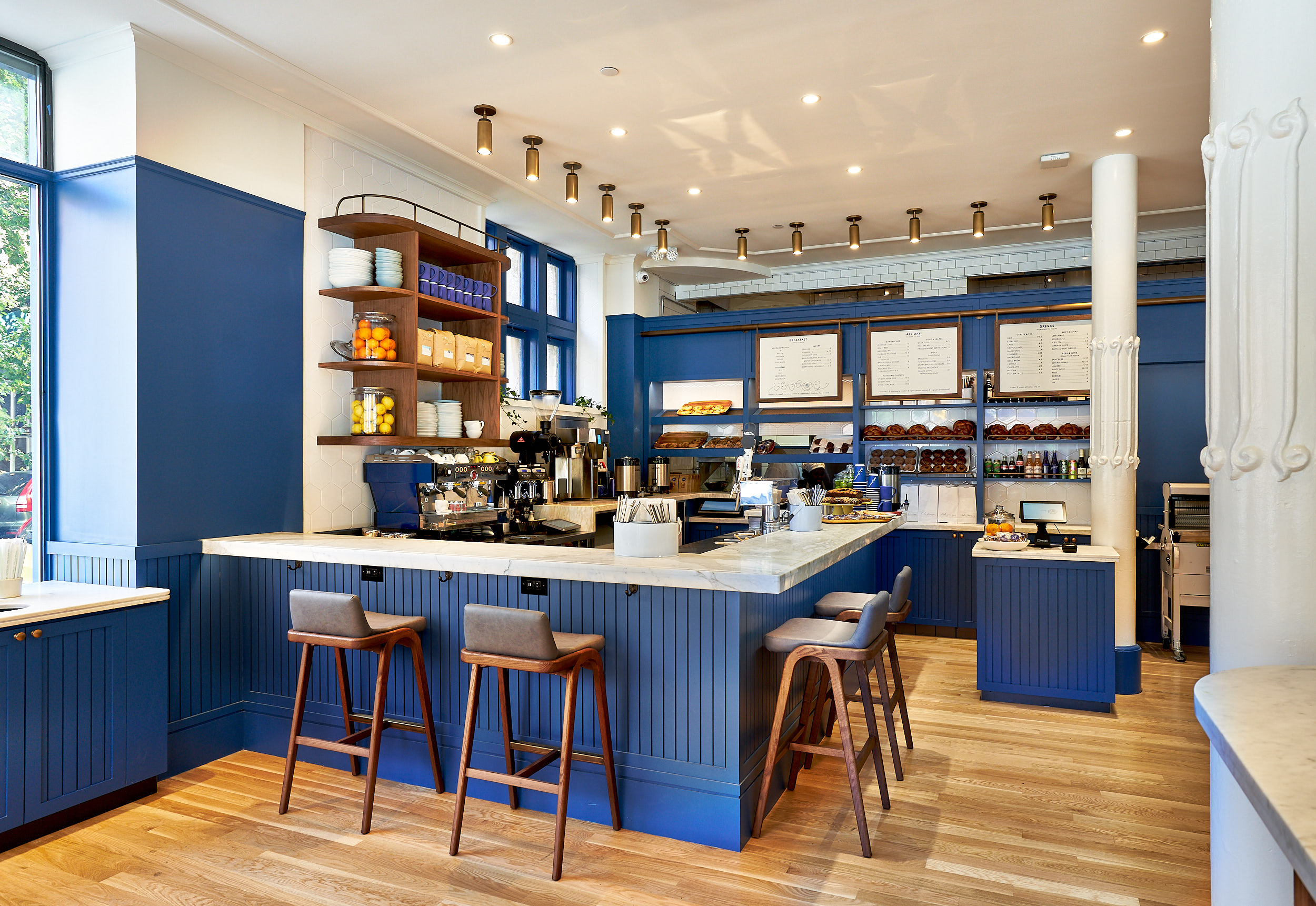 The blue, white, and wood interior of a Daily Provisions cafe