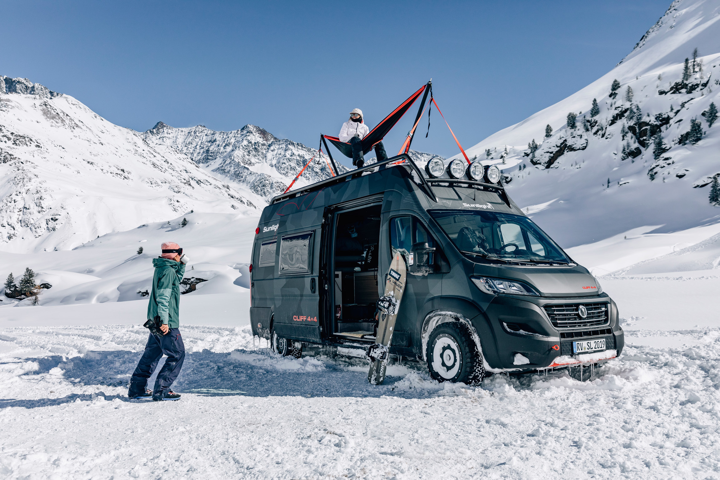 A gray camper van sits in a snowy valley below mountains and a blue sky. The side door of the van is open with a snowboard standing next to it; one person in snow gear is walking towards the van and another person sits on the roof in a hammock.