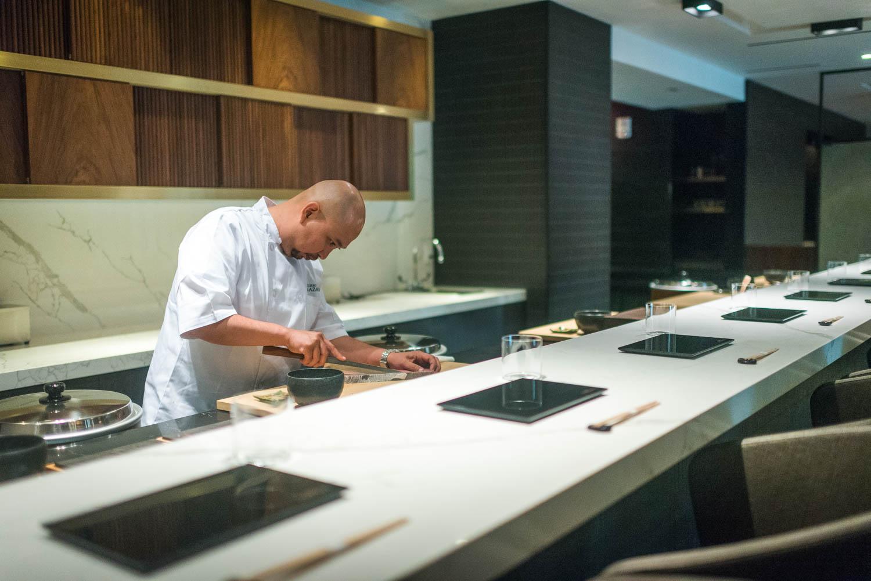 A man, Daisuke Nakazawa, slices fish behind a sushi counter set with black, rectangular plates and chopsticks.