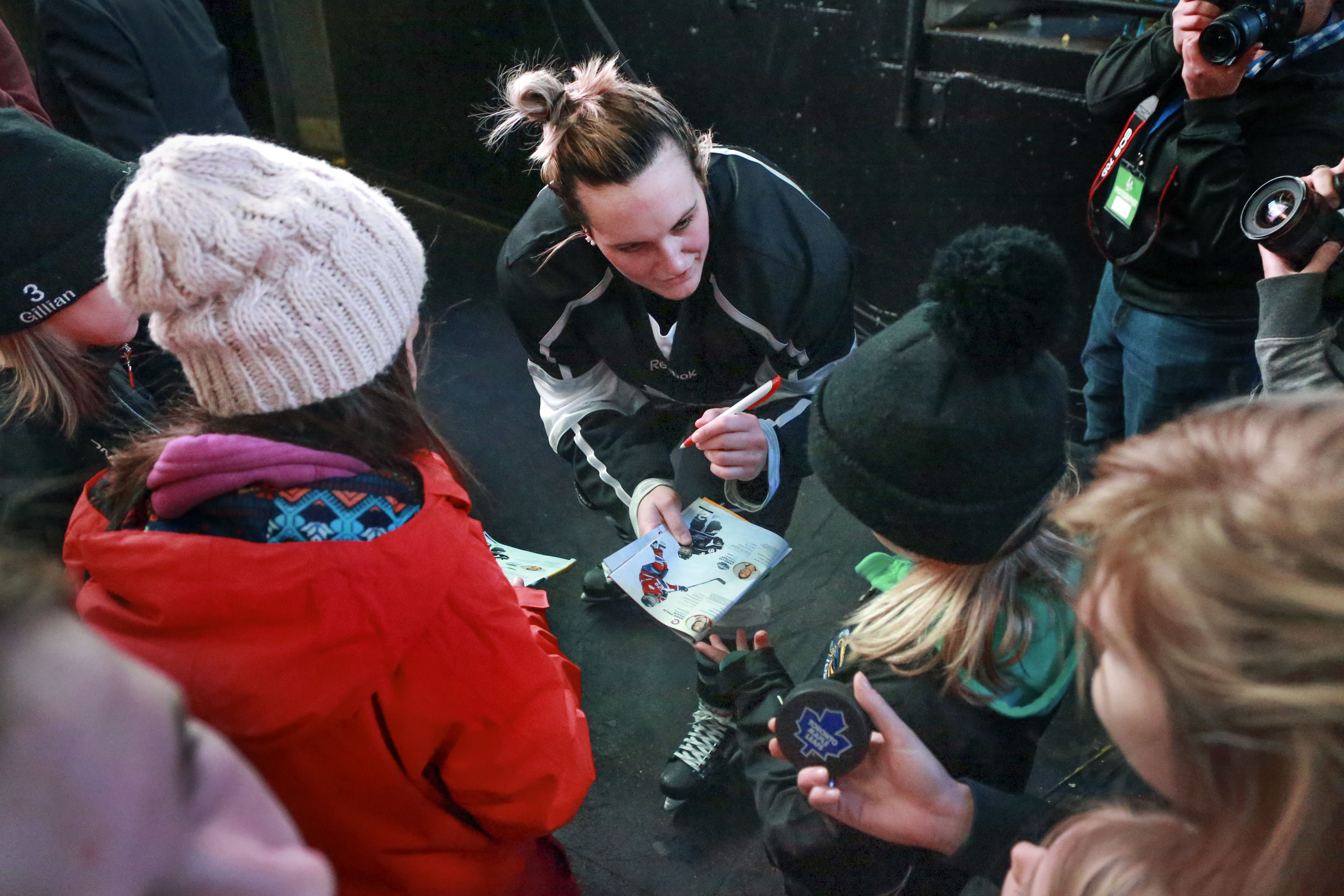 Marie-Philip Poulin signs autographs for young fans.