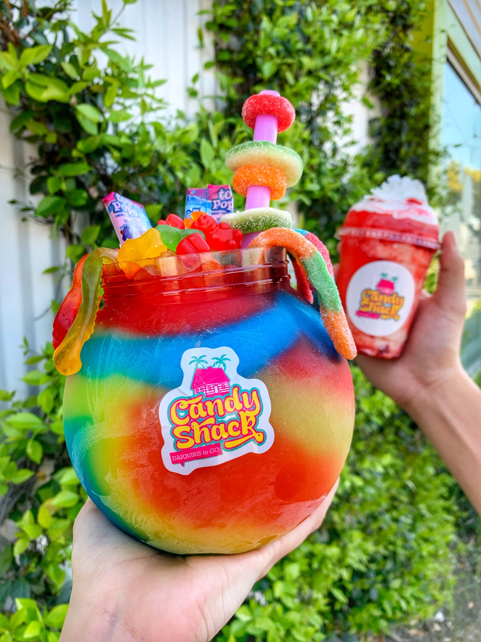 A fishbowl of frozen daiquiri garnished with candy