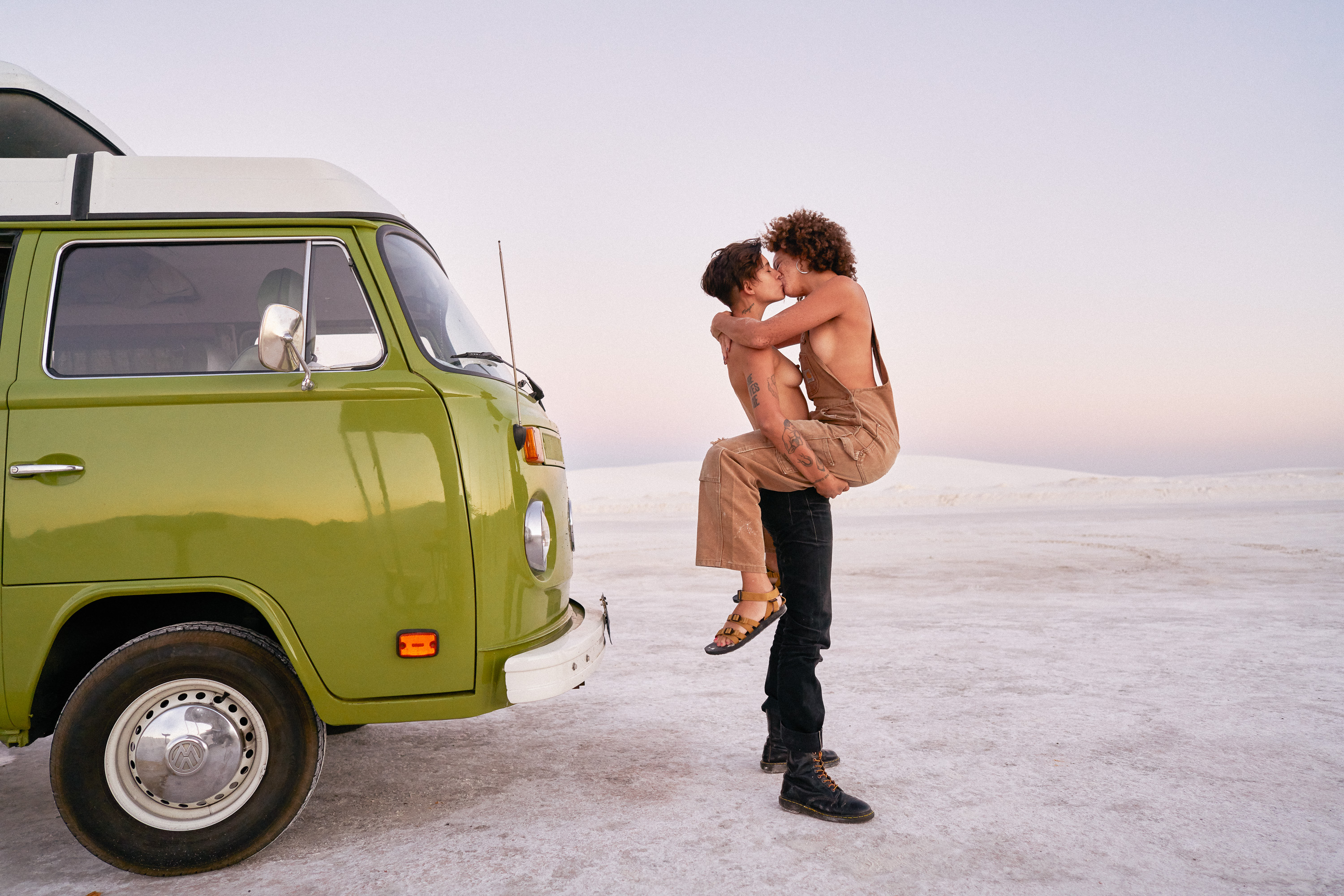 An avocado green 1970s VW Westfalia parked in the desert with a couple kissing in front of it.