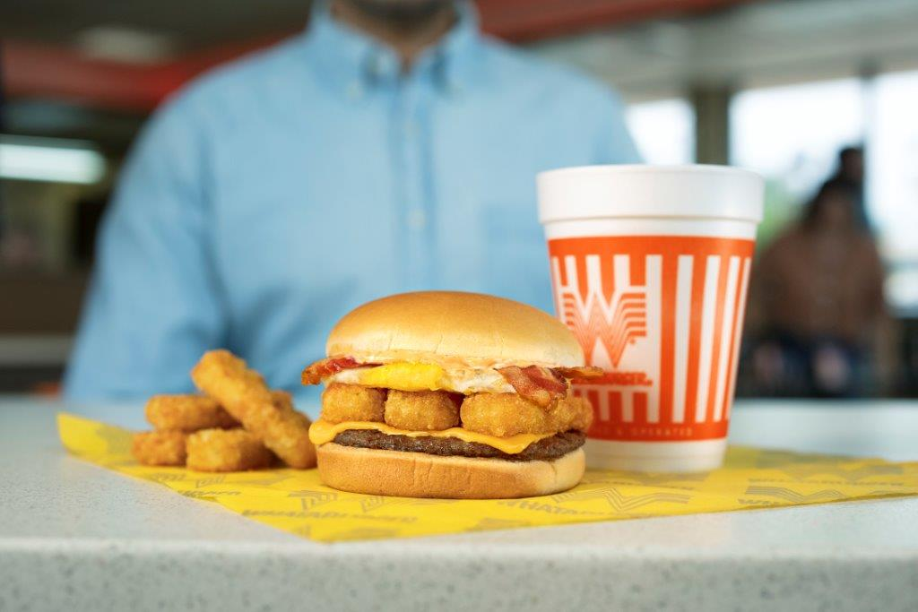 A burger with bacon, a fried egg, hash browns, cheese, and patty on a yellow paper with hash brown sticks and a giant drink cup with orange and white markings in front of a blurry person