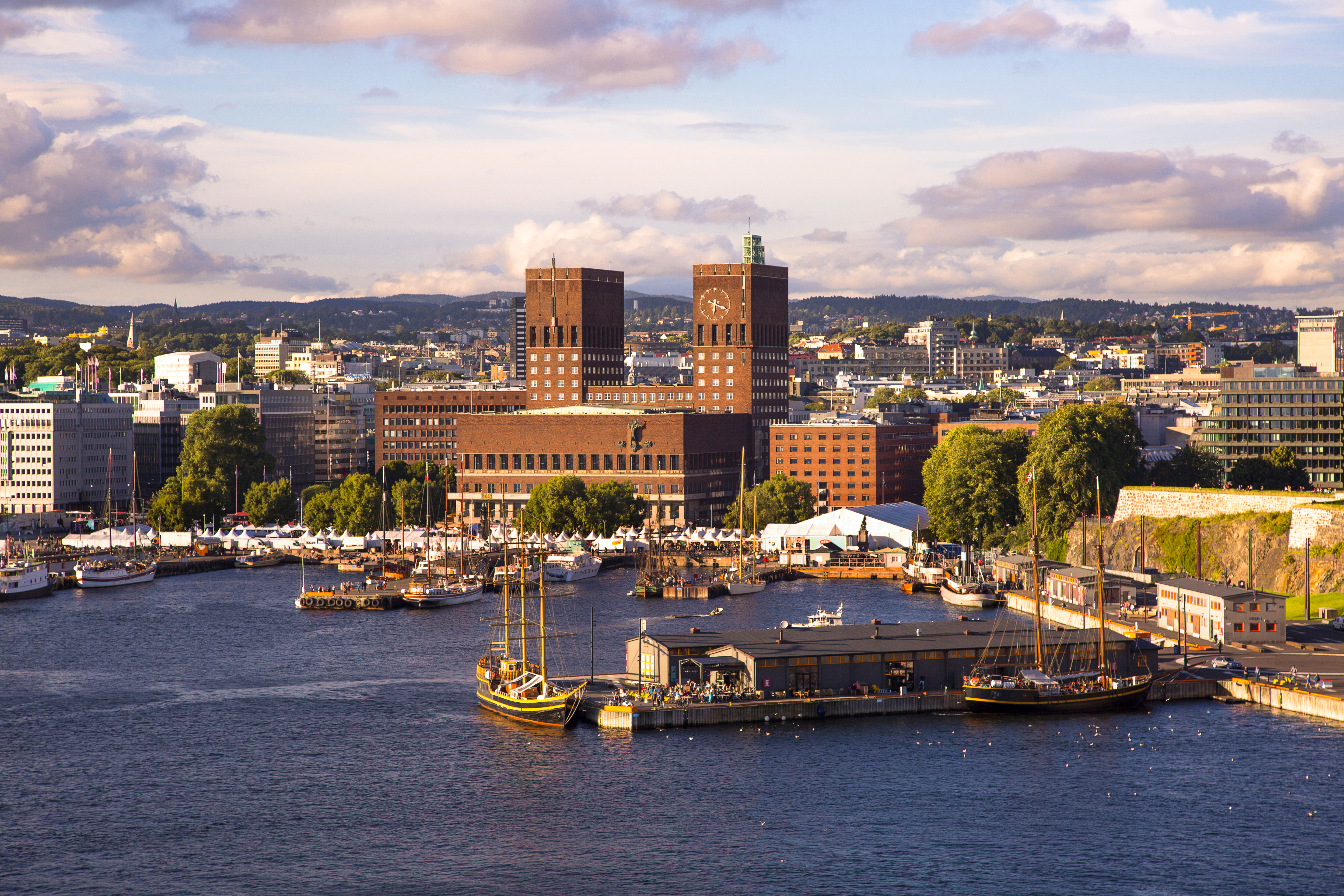An aerial view of a large brick building with two identical towers on its roof, sitting along a waterfront lined with trees and shorter buildings.