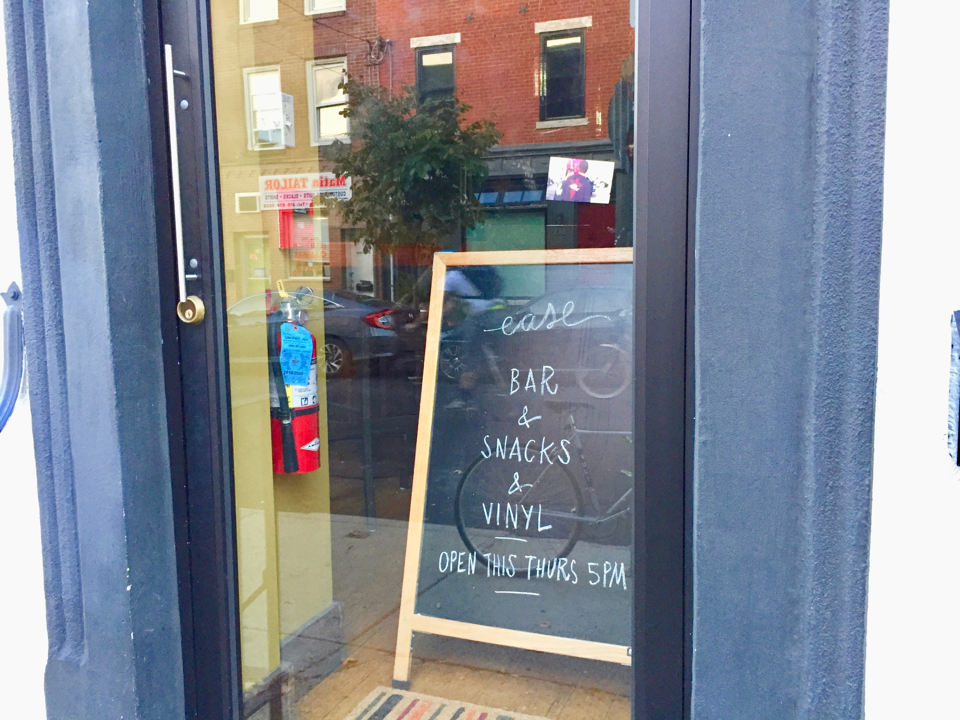 door of bar with sign that says bar, snacks, vinyl