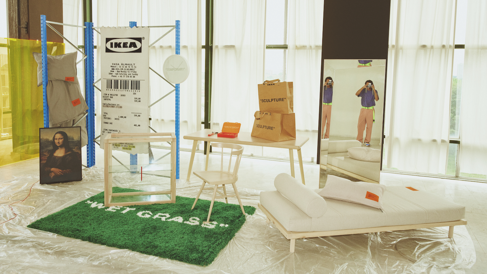 """A group of furniture and decor items, including a green rug that says """"Wetgrass"""" and a rug made to look like a shopping receipt."""
