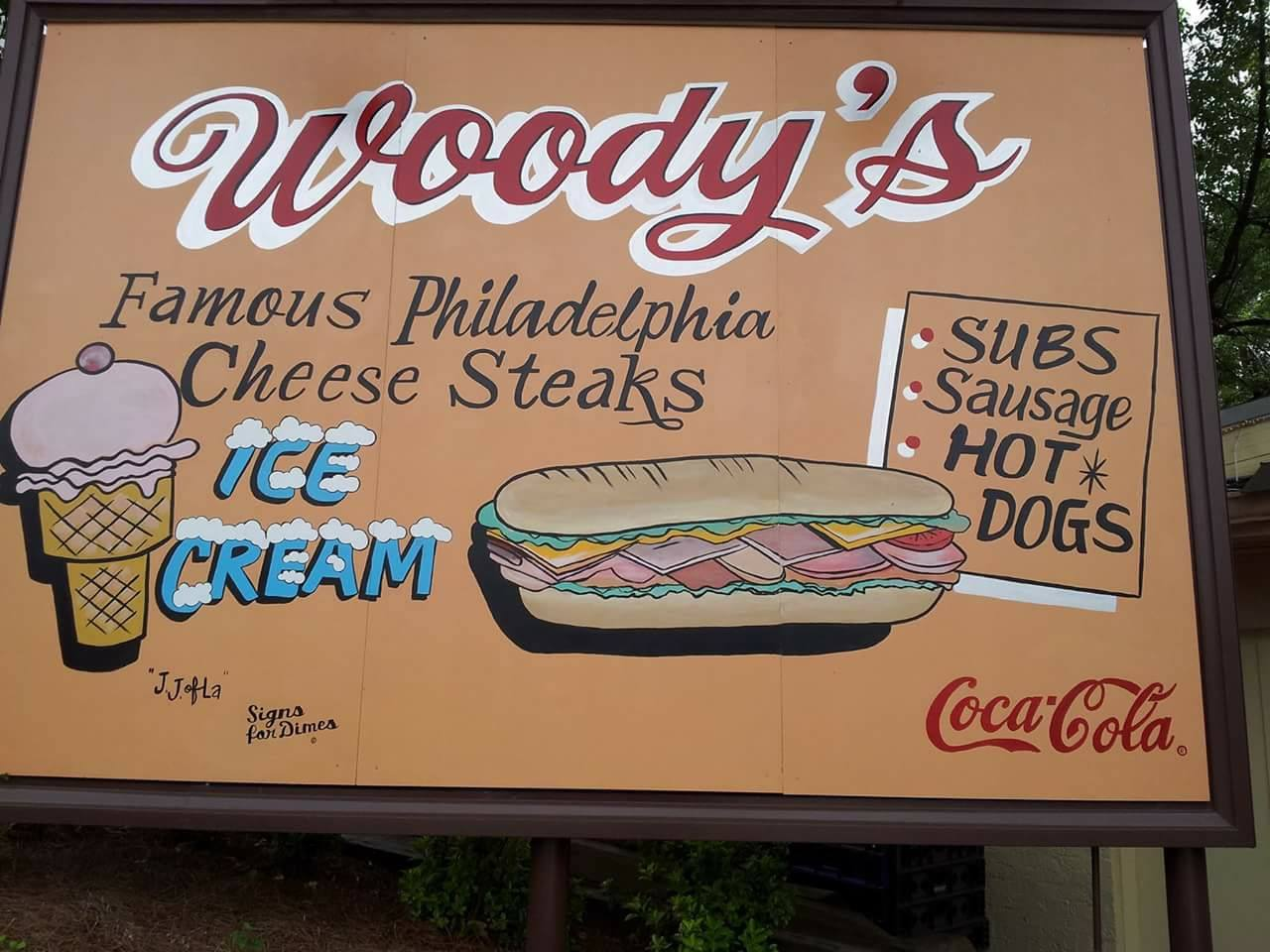 The Woody's famous Philadelphia cheese steaks sign with a painted ice cream cone, sandwich, and the Coca Cola logo