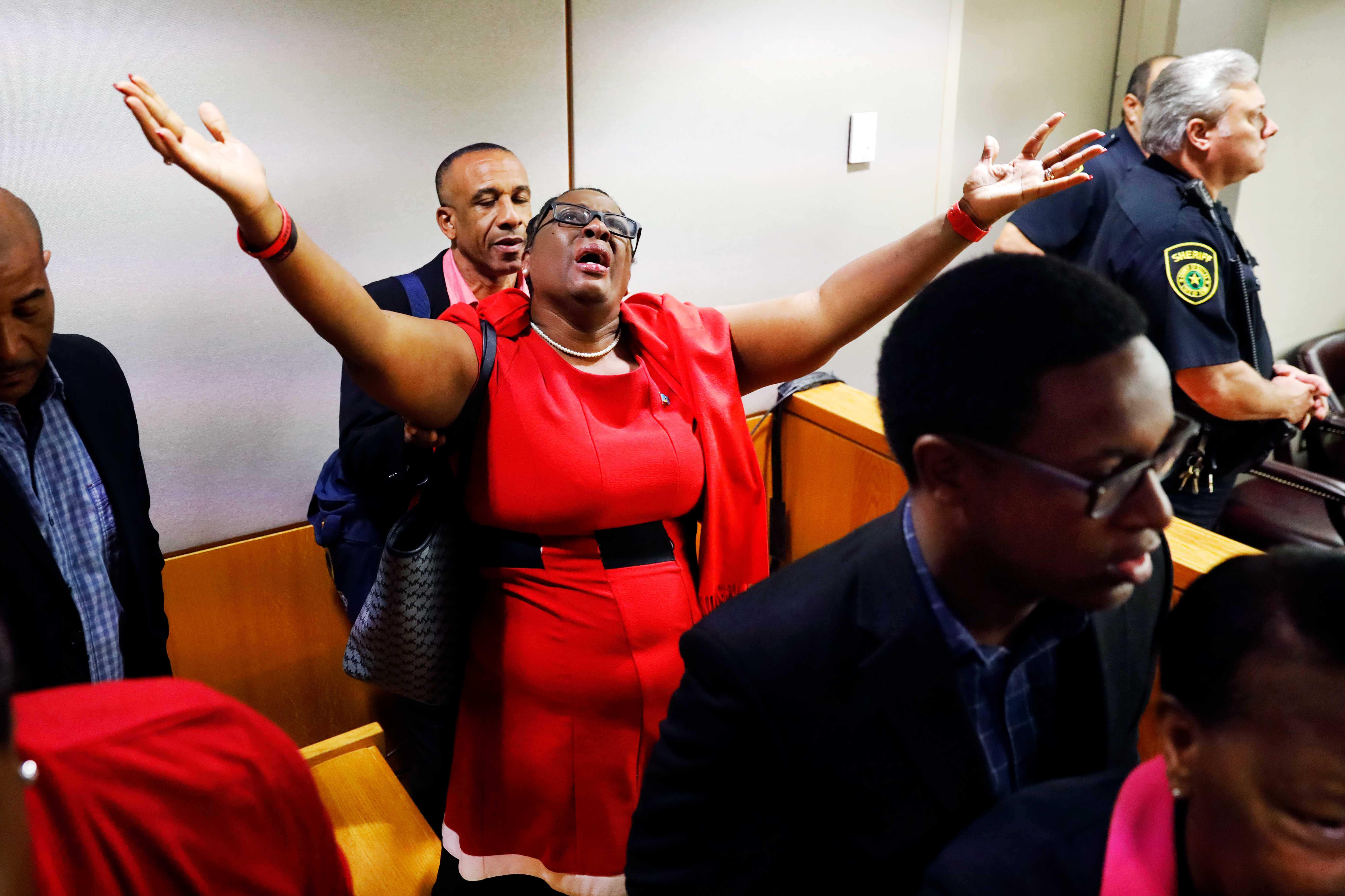 A woman wearing all red throws her hands in the air.