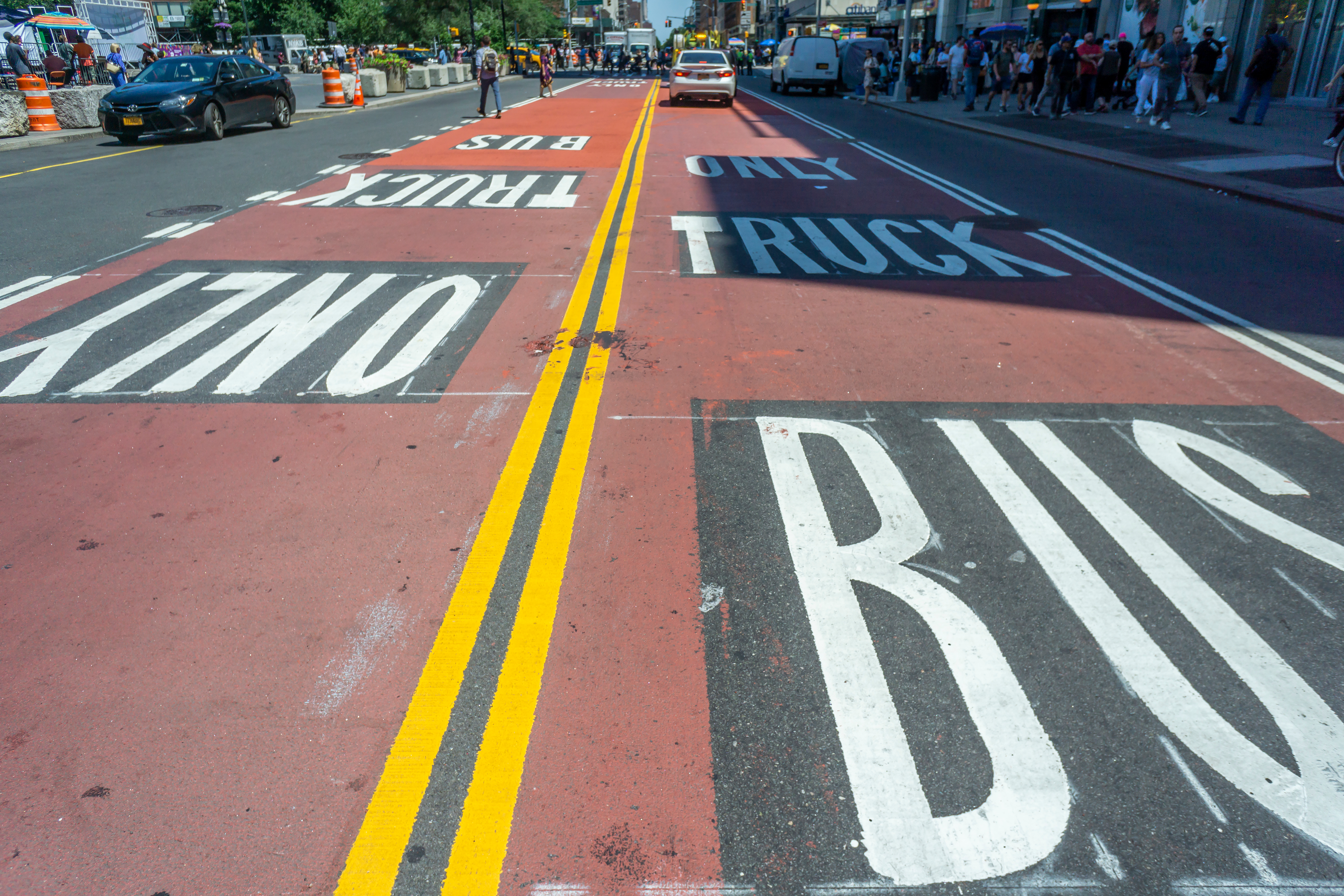 """A street is painted with a red bus lane that states """"Only Truck Bus."""""""