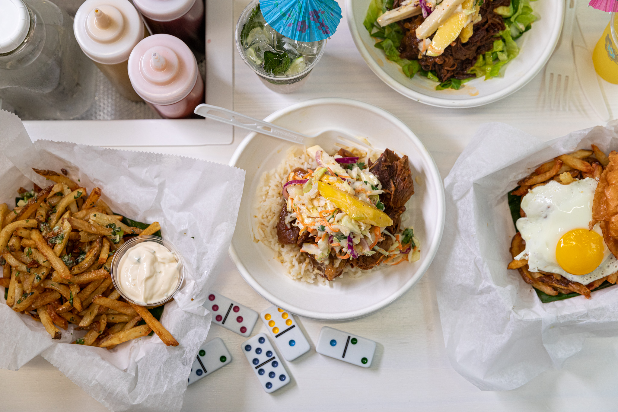 Garlic cilantro fries, a rice bowl, and a burger with a fried egg and shoestring fries on a white table surrounded by dominos, squeeze bottles of sauce, and a mojito.