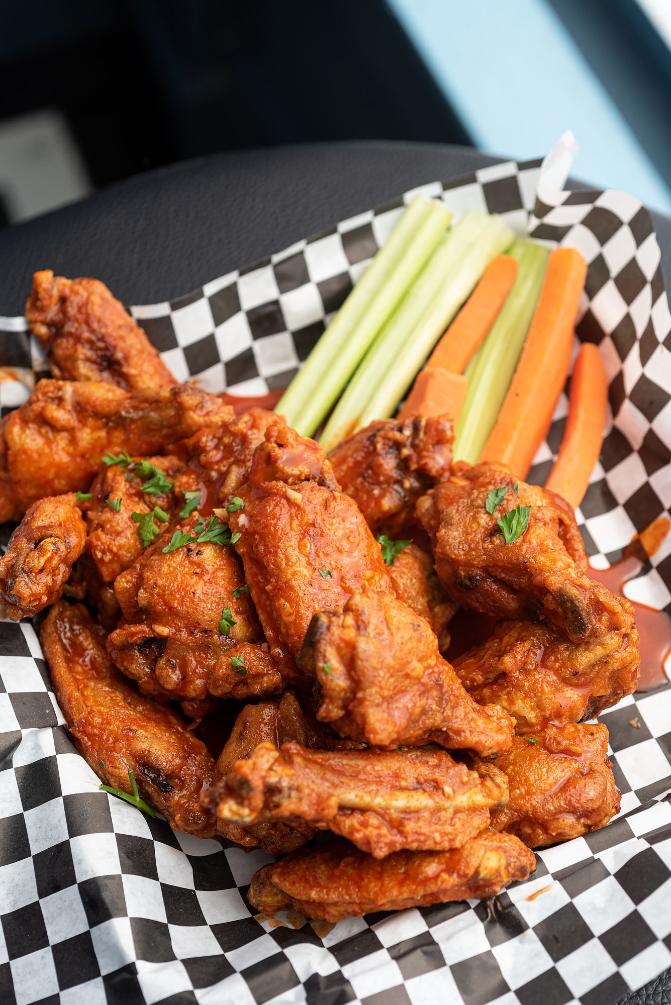 Buffalo chicken wings with carrot and celery sticks in a basket at The Greyhound.