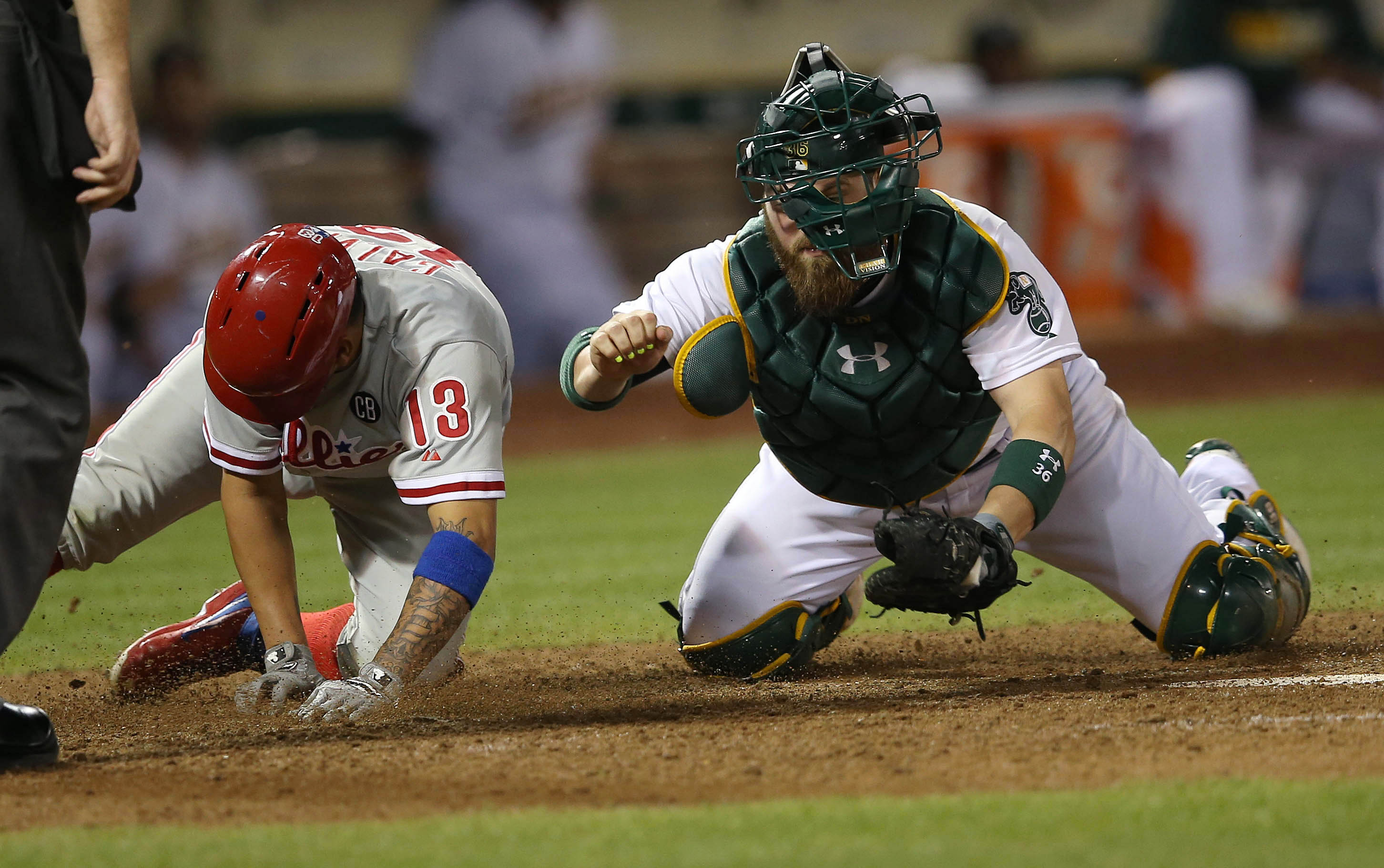 Oakland Athletics catcher Derek Norris (36) loses his mask as he tags out Philadelphia Phillies third baseman Freddy Galvis (13) in the eighth inning of their MLB game at O.co Coliseum in Oakland, Calif., on Friday, Sept. 19, 2014. (Jane Tyska/Bay Area Ne