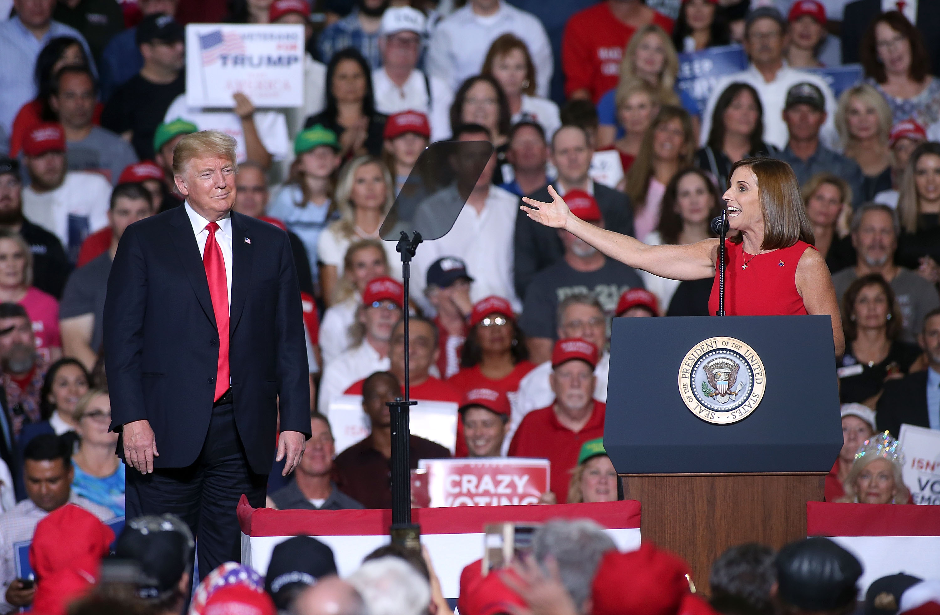 Representative Martha McSally holds out her arm in a gesture toward Donald Trump onstage at a political rally.