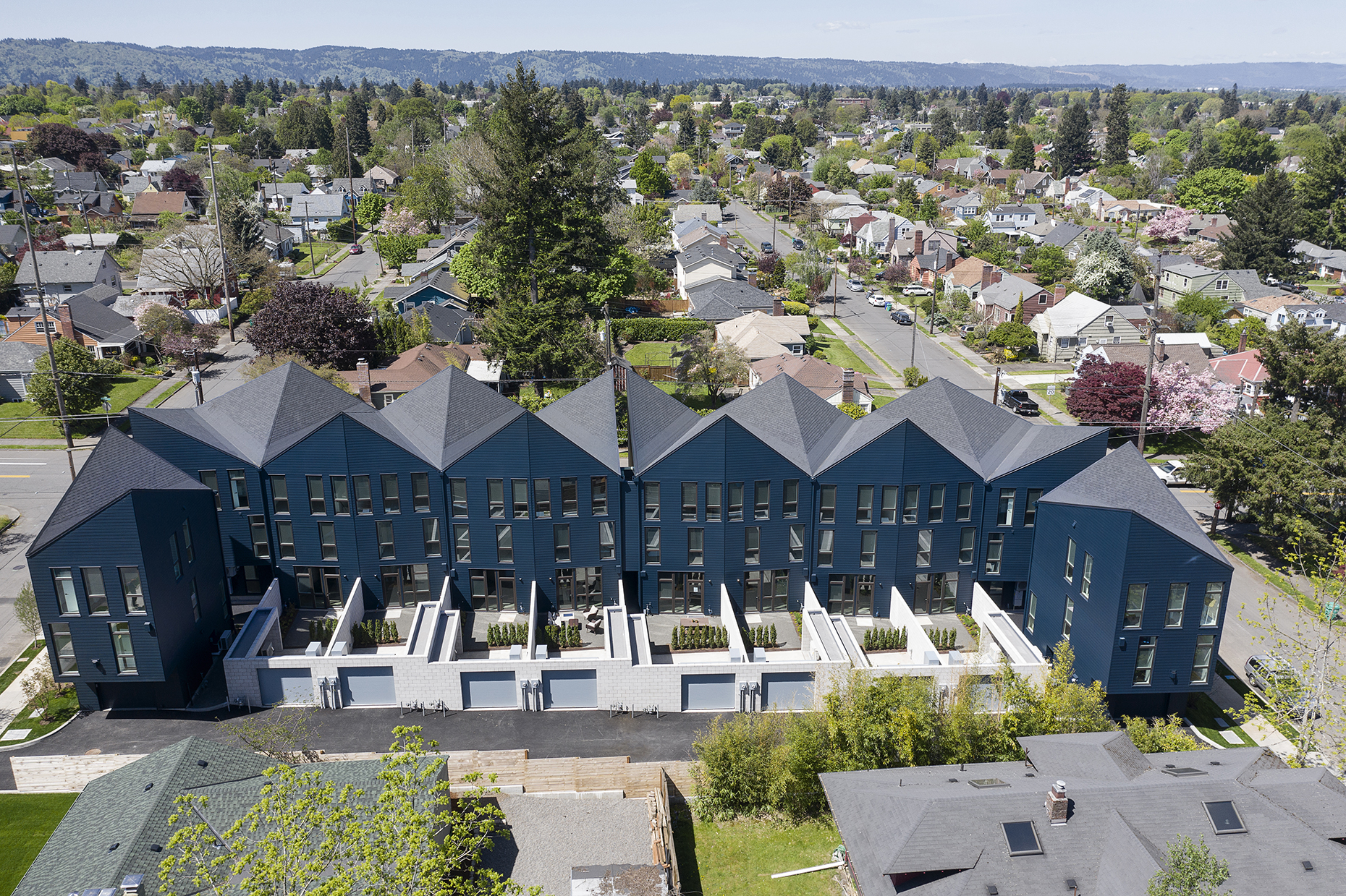 Aerial view of C-shaped townhouse complex with a roofline that peaks and dips.