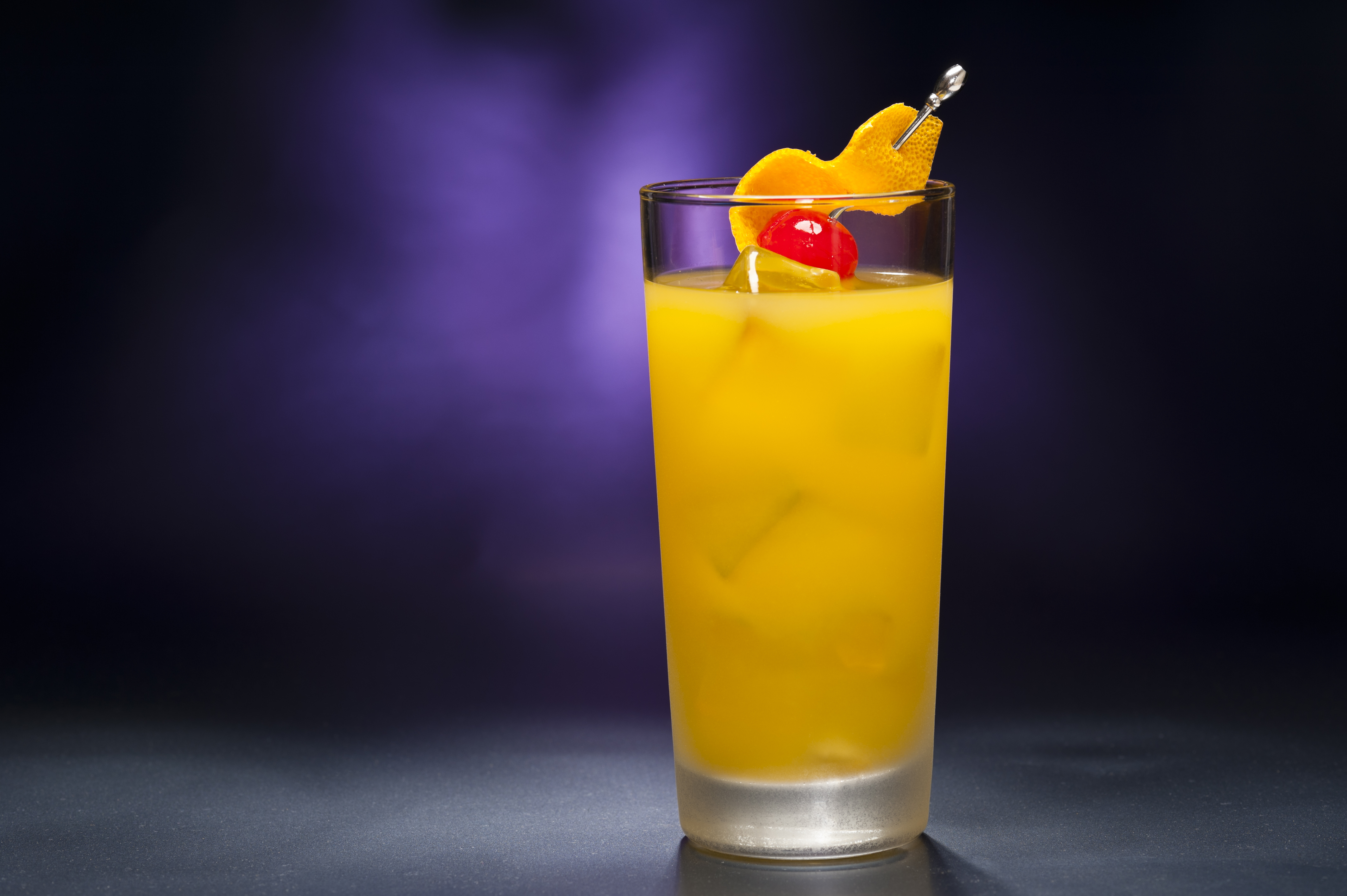 An orange highball cocktail garnished with a cherry and an orange peel in front of a purple background