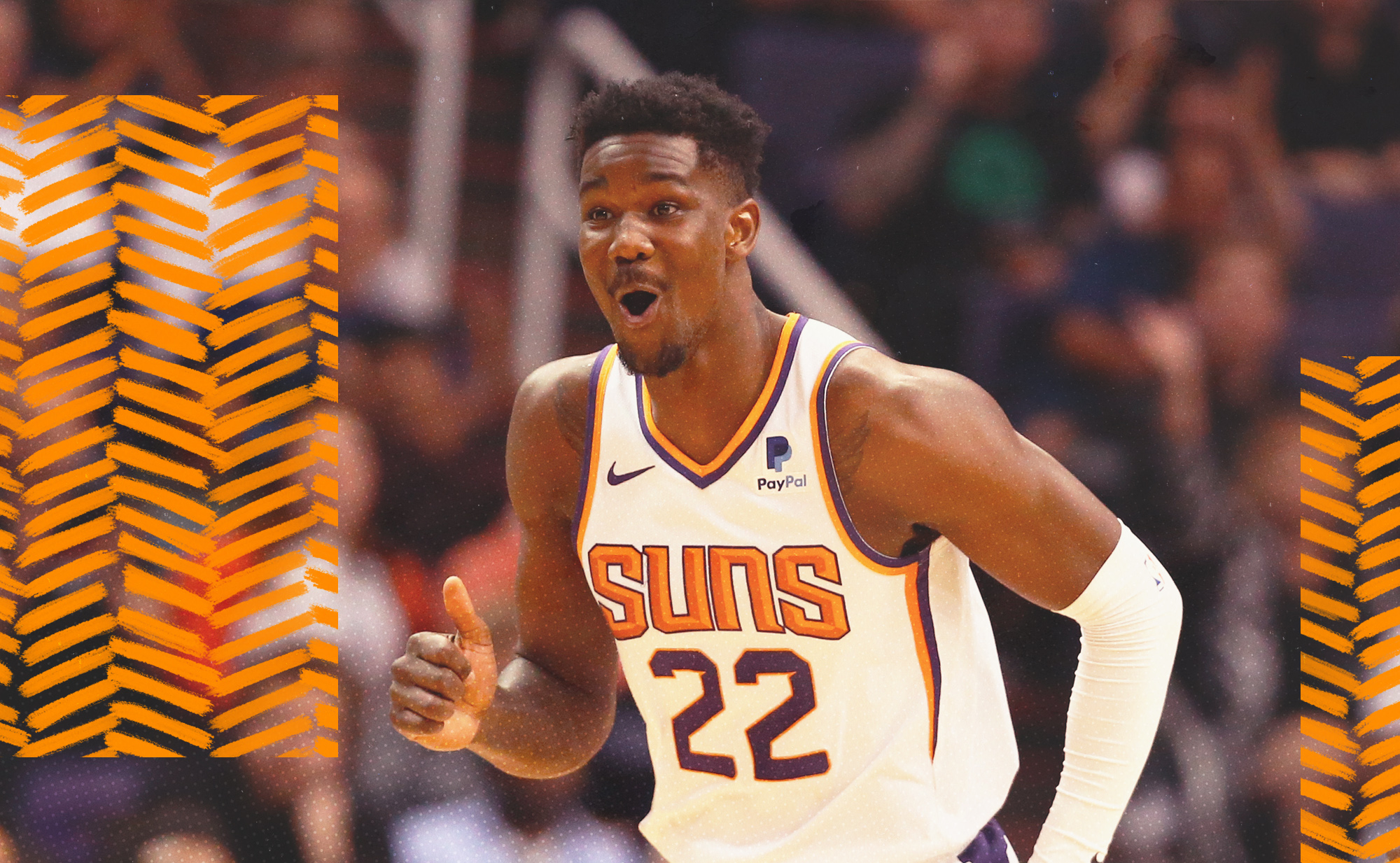 Deandre Ayton smiles as he runs down the court for the Phoenix Suns.