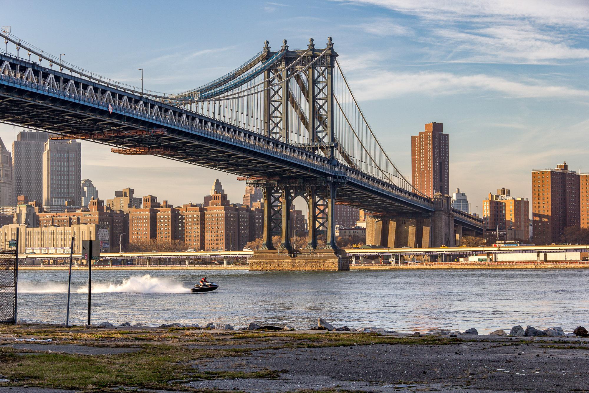 A dark blue metal bridge spans over the East River.