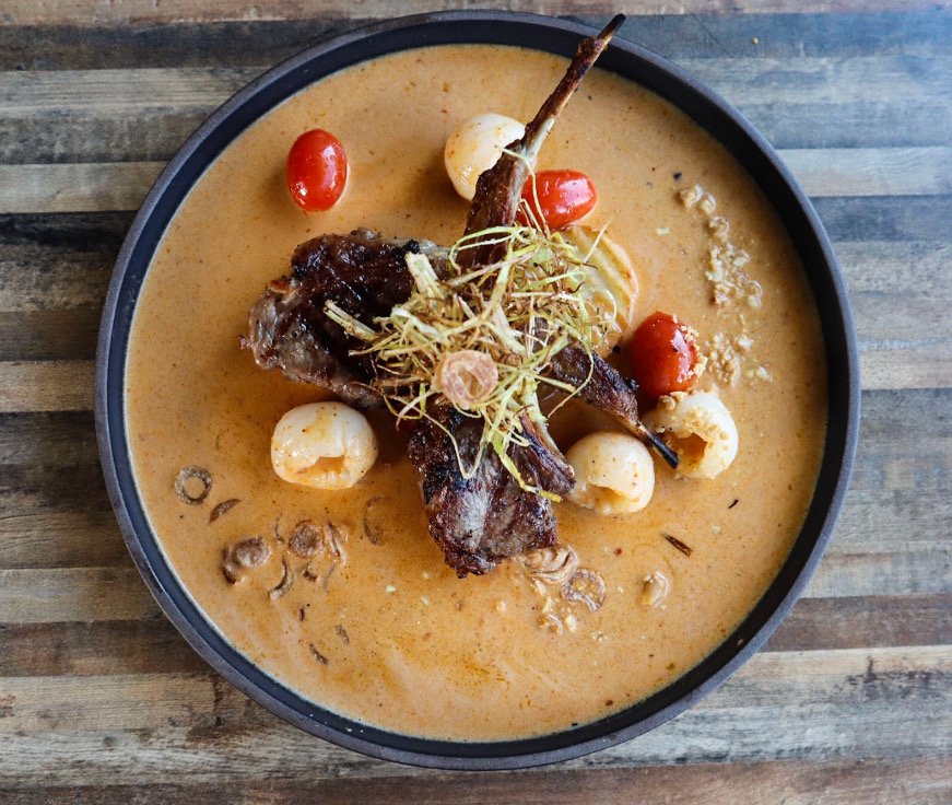 A photo of a bowl of lamb massaman curry from Daughter Thai Kitcehn & Bar consisting of an orange curry broth with large chunks of lamb and cherry tomatoes visible in it