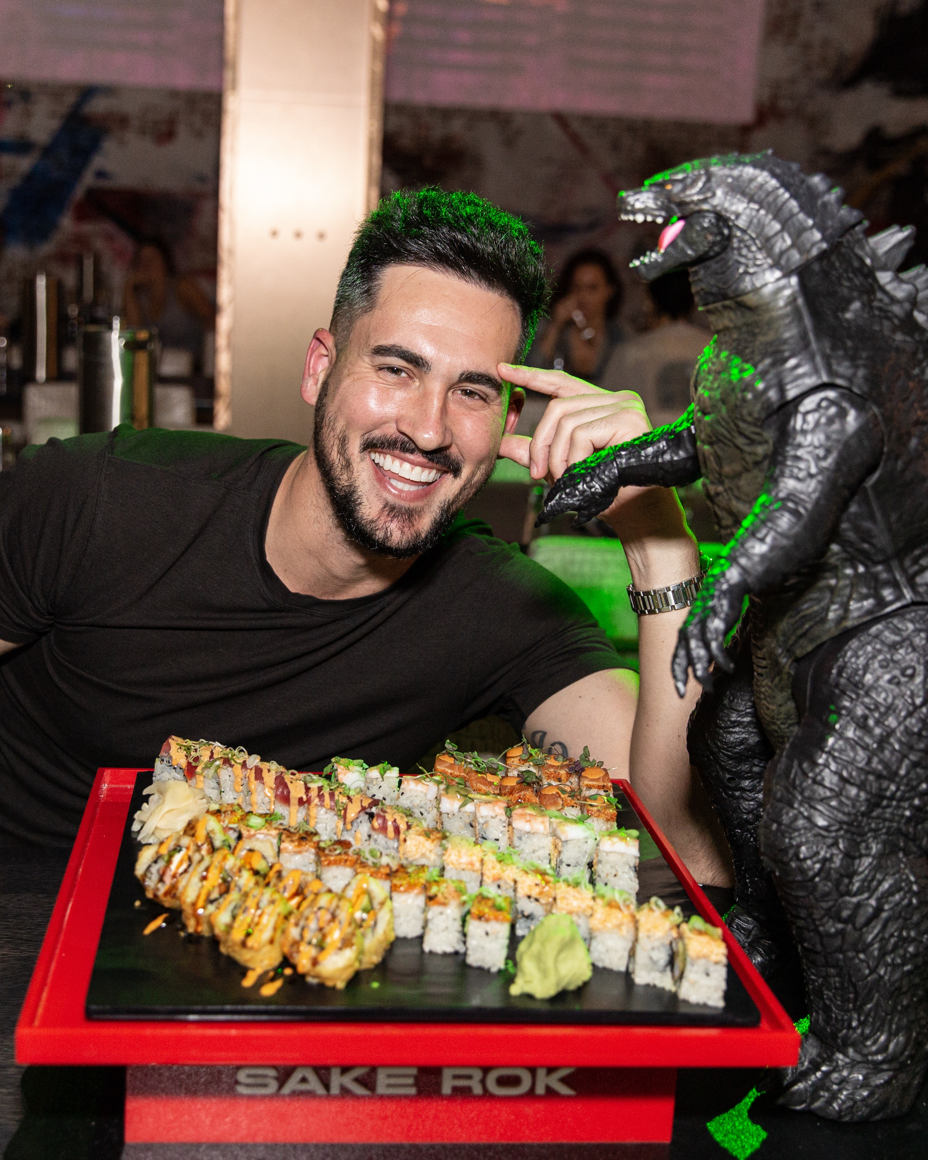 An actor poses next to a replica of Godzilla