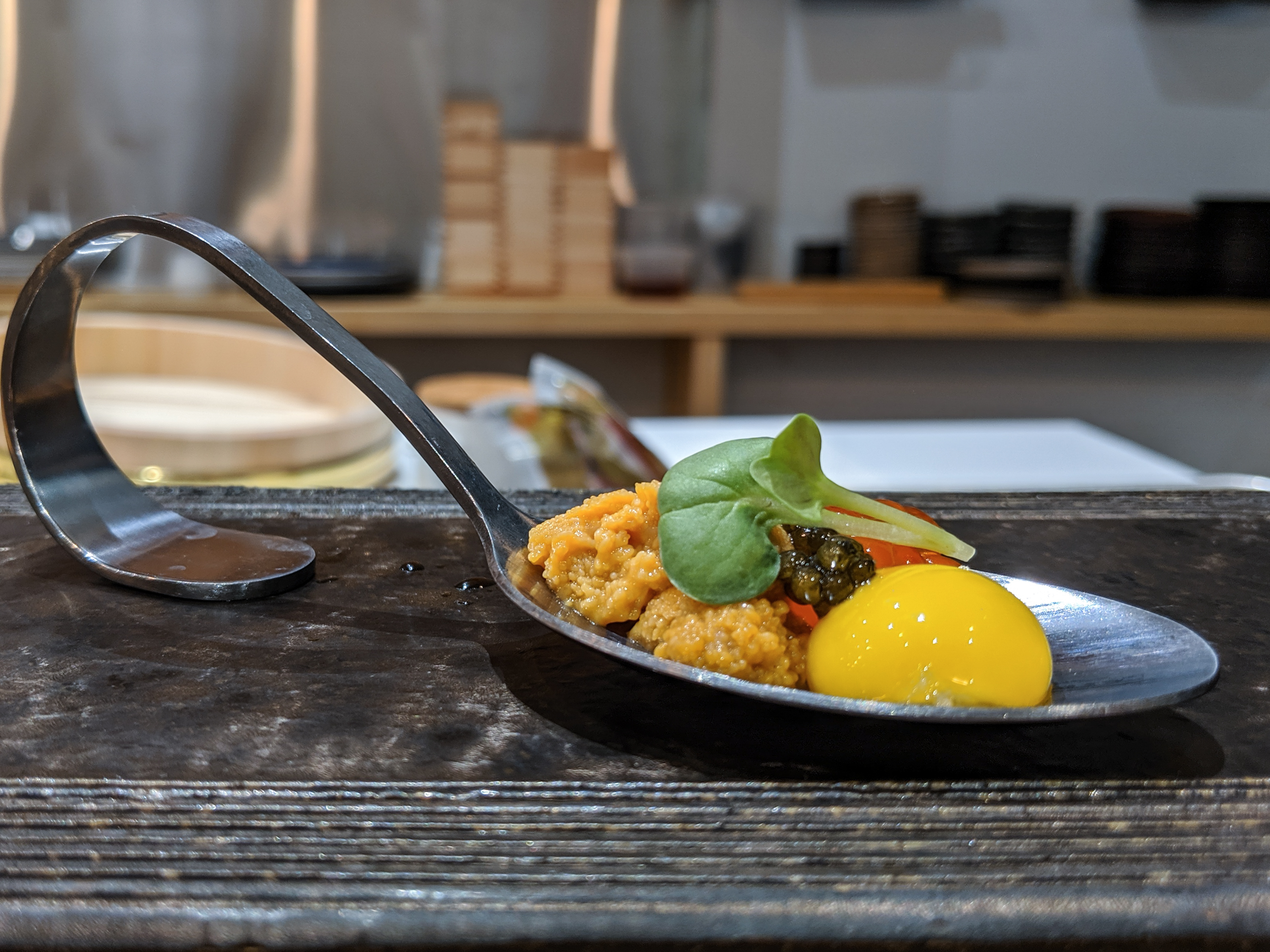 Uni, caviar, and a quail egg yolk are perched delicately on a curved metal spoon
