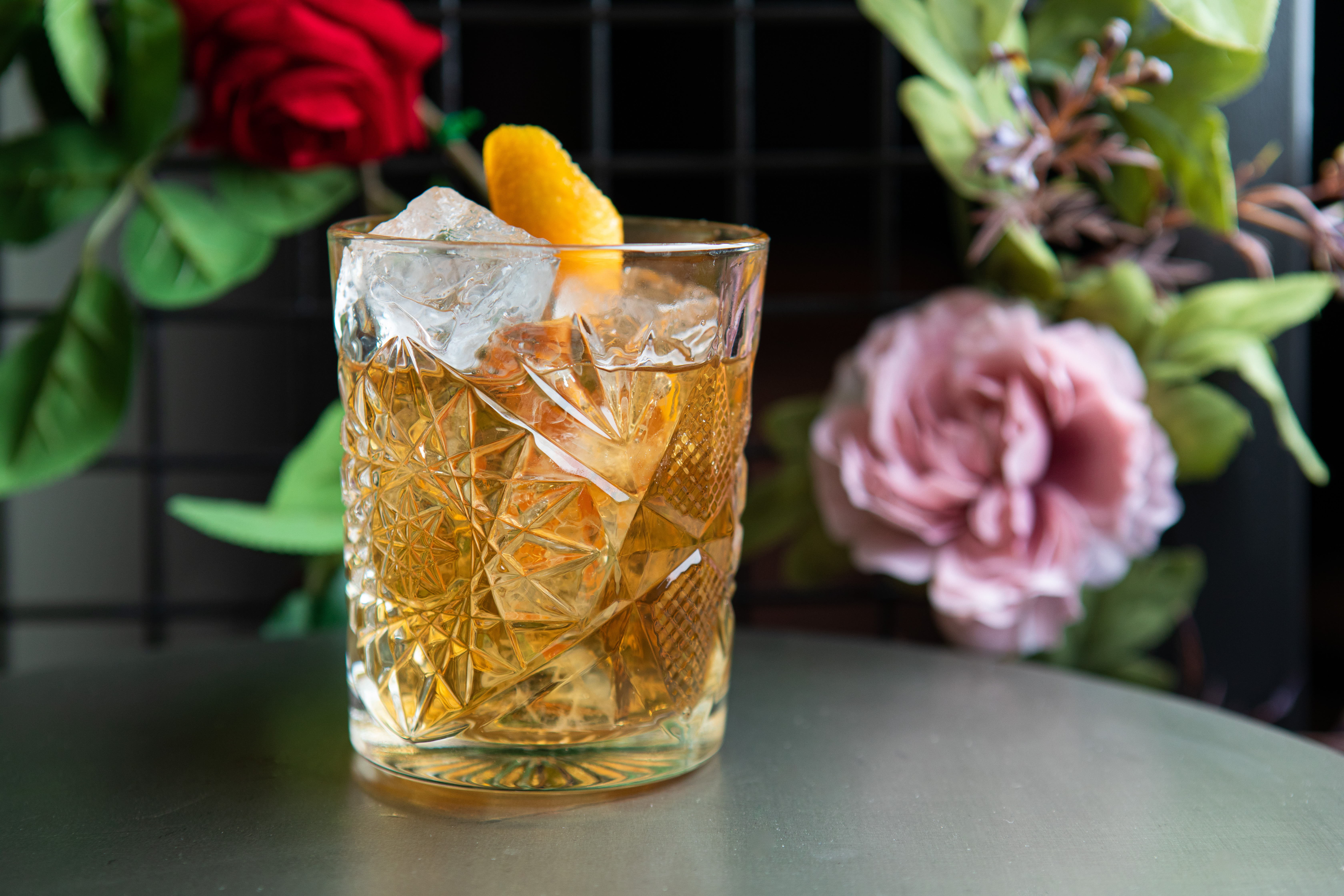 A brown cocktail in a cut crystal glass sits in front of a bouquet of flowers.