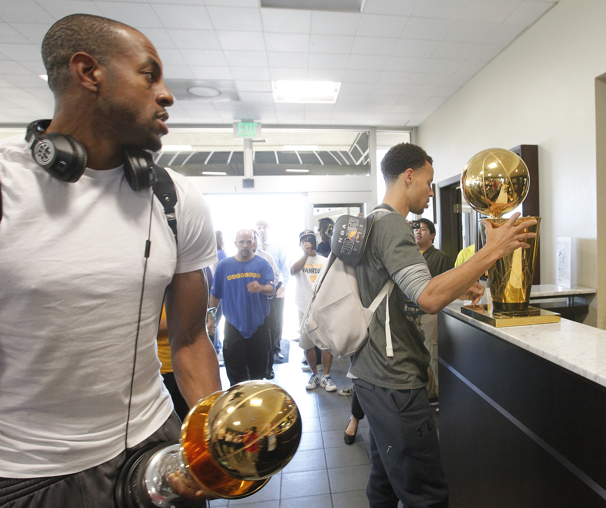 Golden State Warriors forward Andre Iguodala, right, carriers the trophy for being named MVP of the NBA championship and guard Stephen Curry, right, carries the Larry O'Brien NBA Championship Trophy after the team landed in Oakland, Calif., Wednesday, J