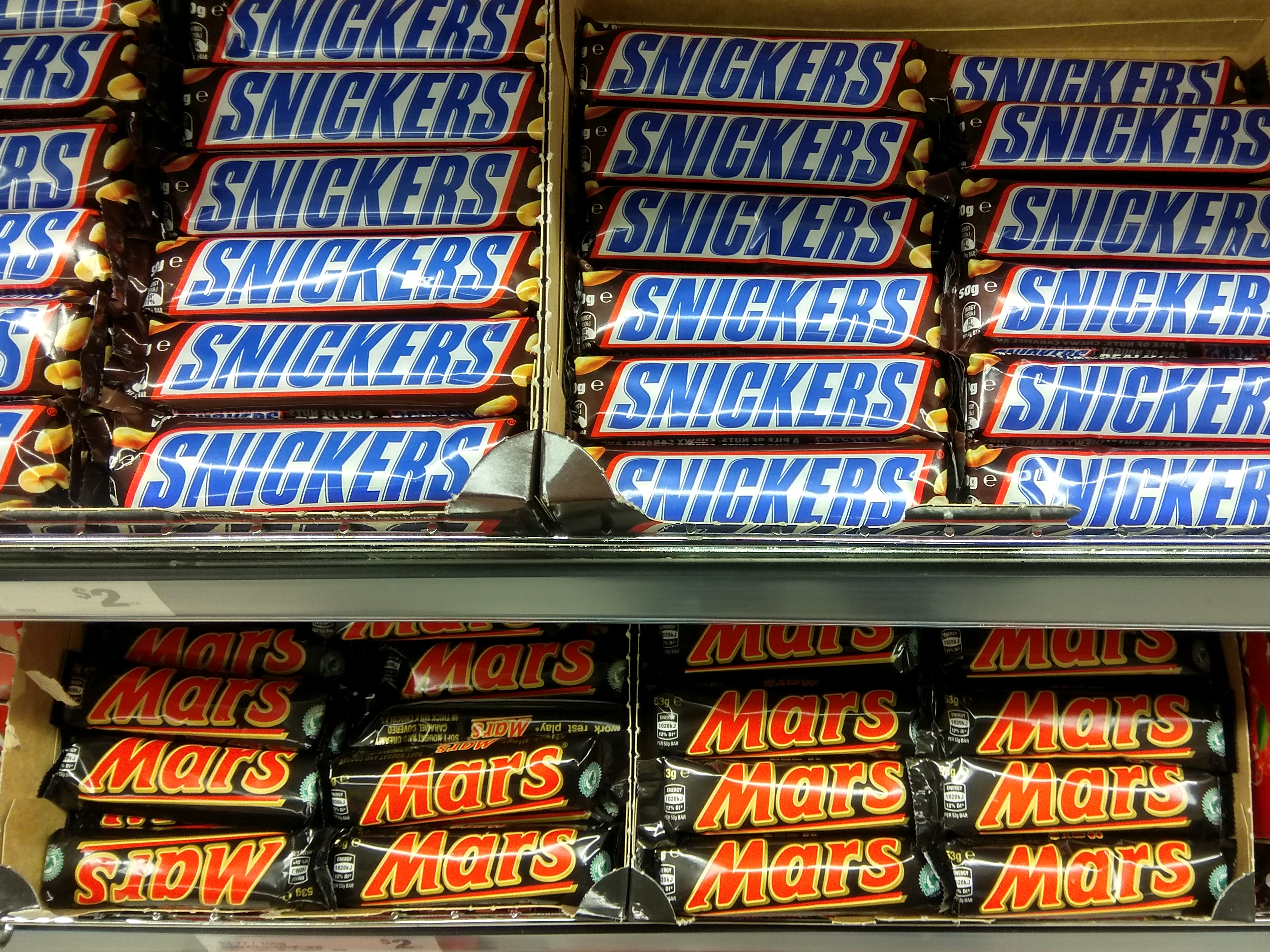 Snickers and Mars chocolate bars on store shelf.