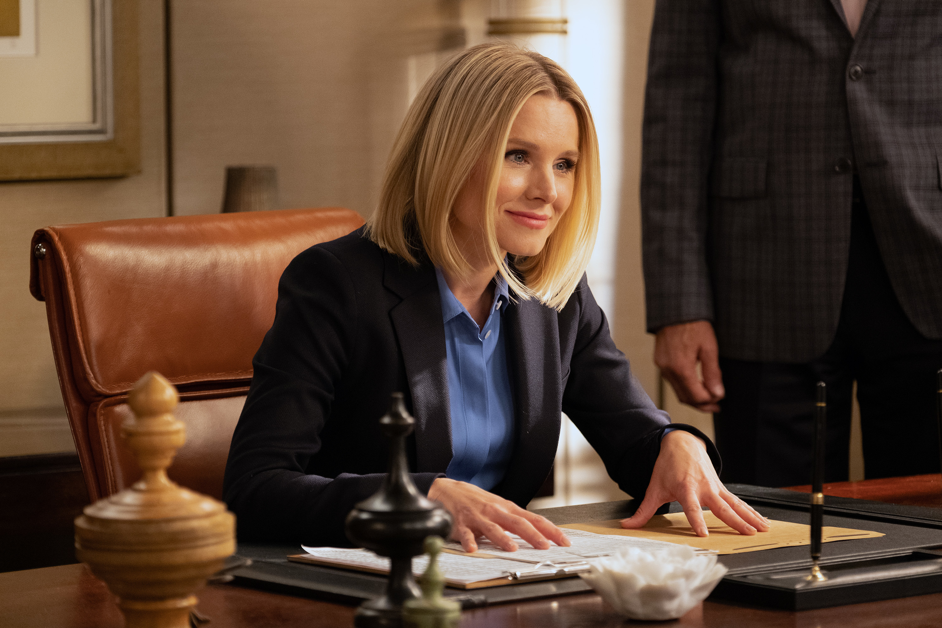 """Kristen Bell as Eleanor in """"The Good Place"""" sits at a desk and smiles."""