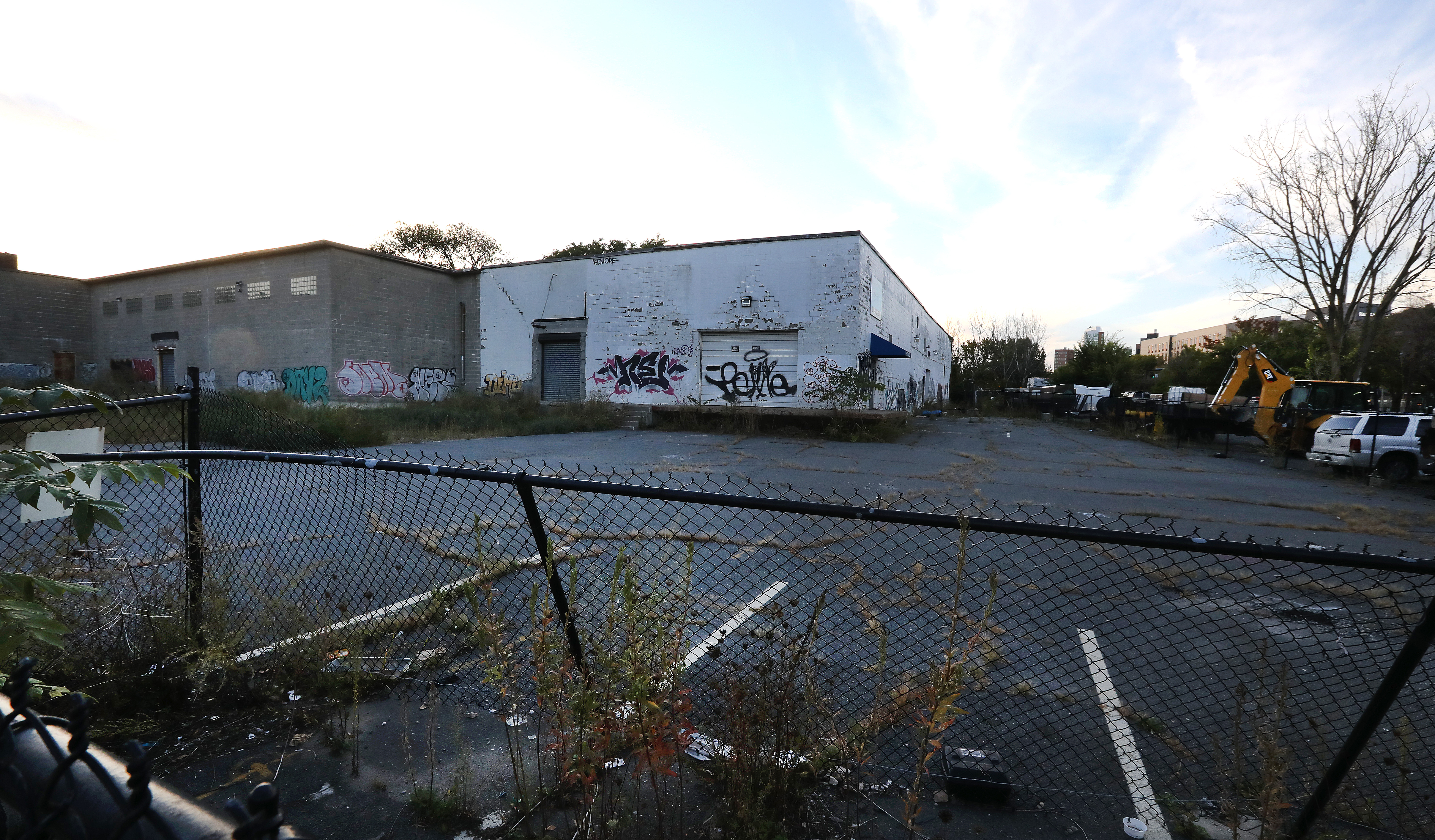 A vacant lot with a fence in front of it and a rundown single-story building at the end of it.