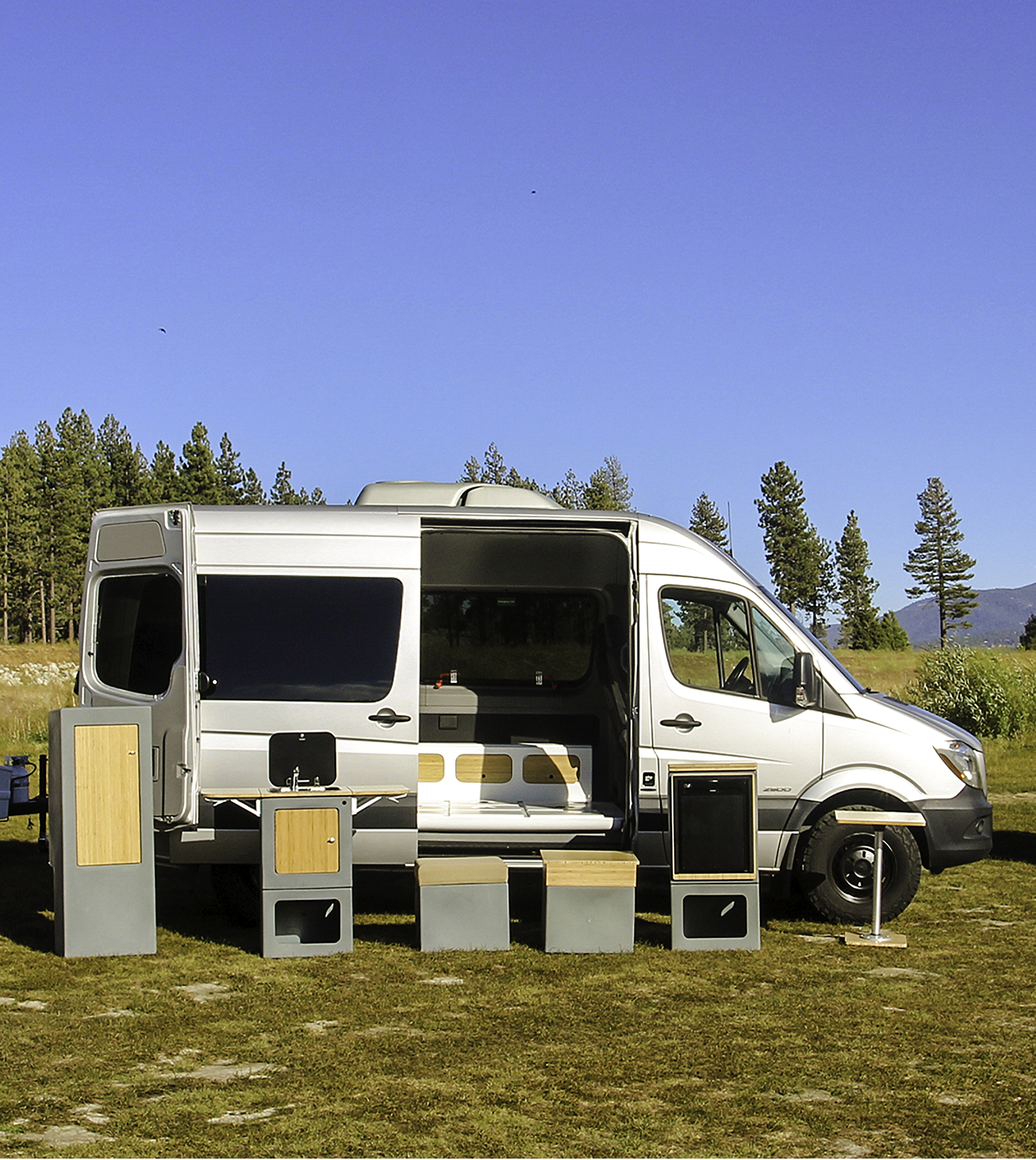 A silver Mercedes Sprinter van sits in a mountainous area with its side door open. Outside of the van are geometric cubes in various shapes that showcase the Happier Camper conversion kit.