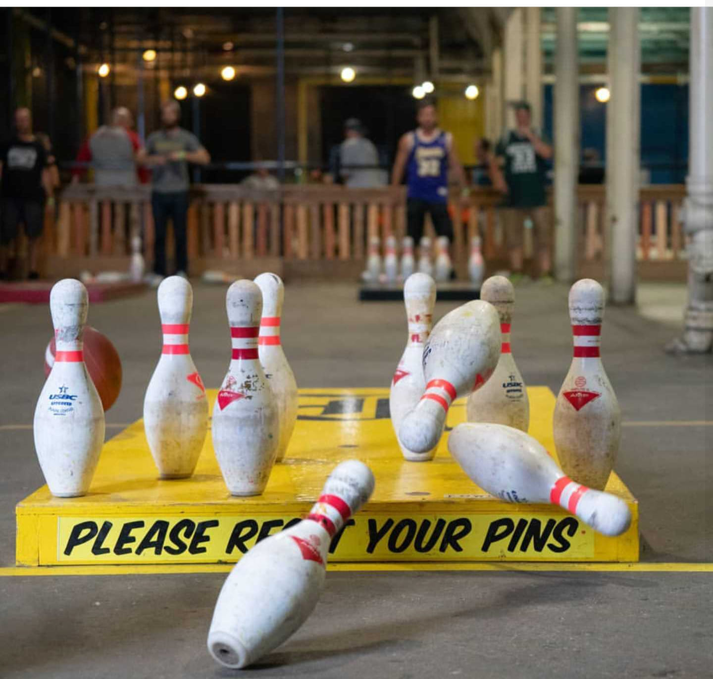"A yellow wooden platform set with bowling pins, three falling bowling pins, and a black painted ""please reset your pins"" sign"