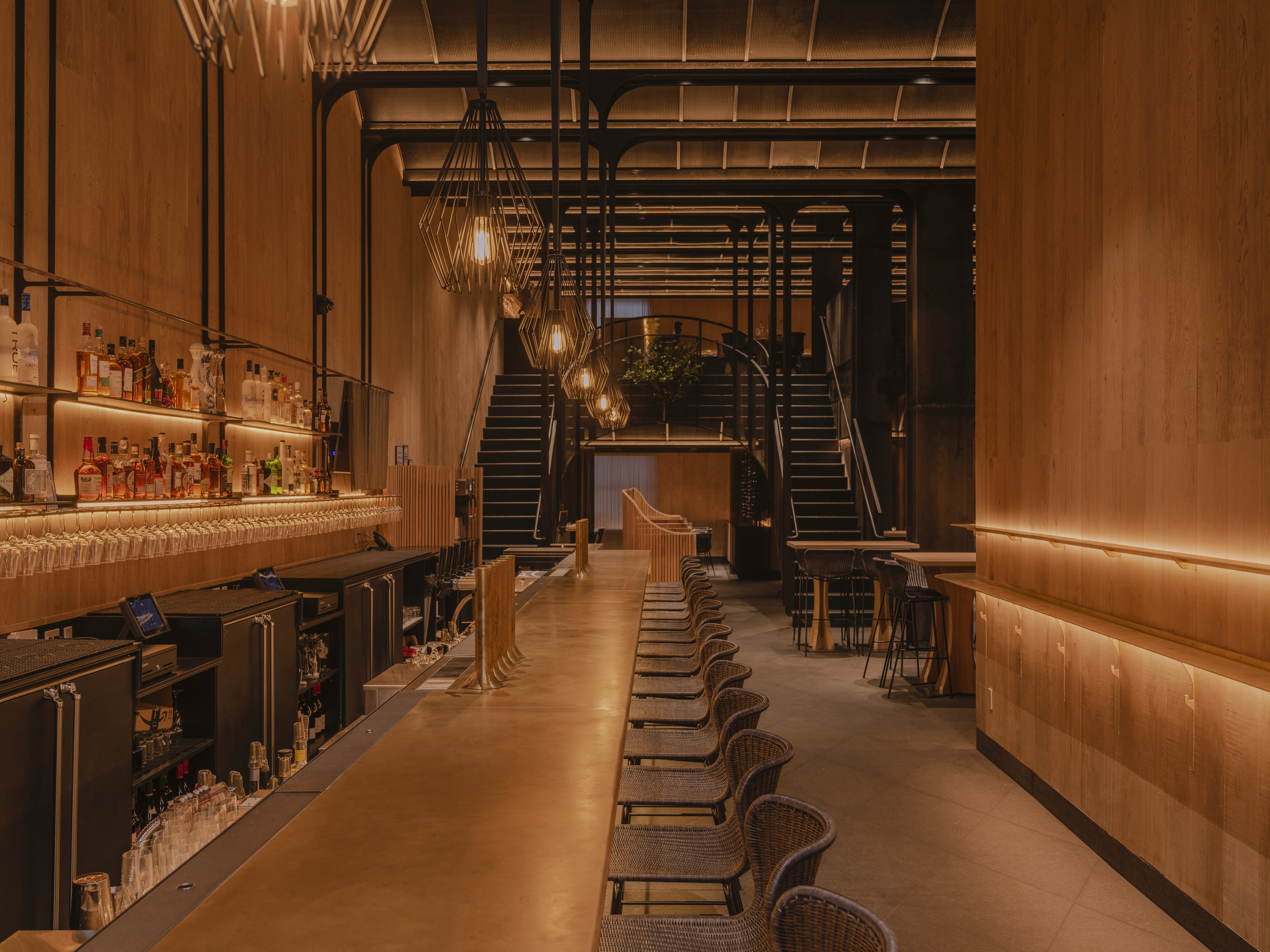 A view of the long bar at Asset with the restaurant beyond