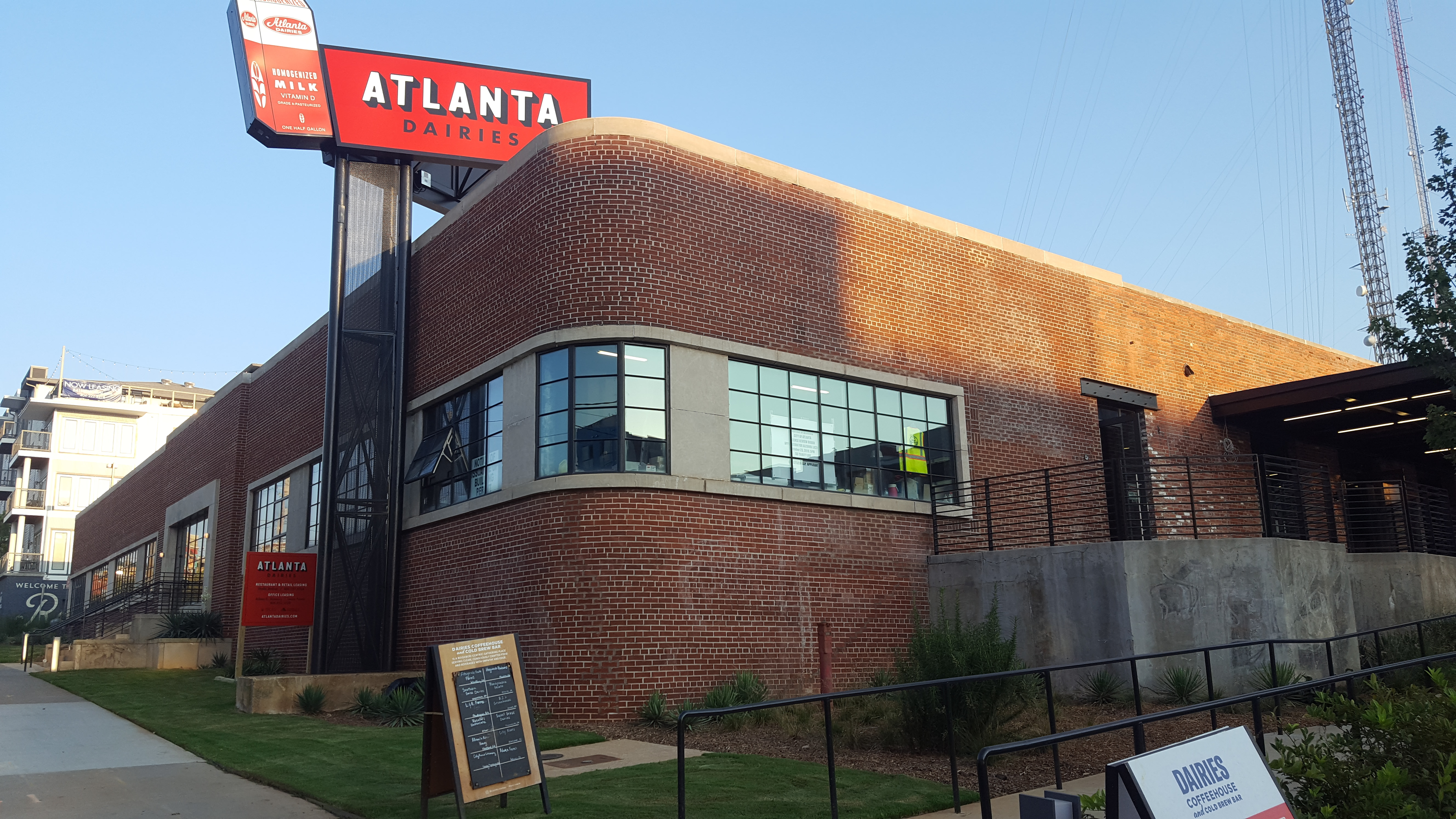 "a brick building with a rounded corner is topped by a vintage sign with a milk carton that reads, ""Atlanta Dairies."""